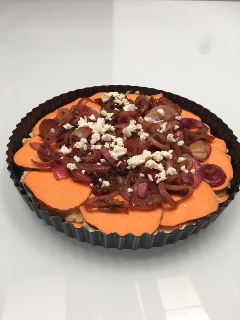 Add your caramelized onions to the center of tart, and sprinkle with a bit of feta for decoration before baking.