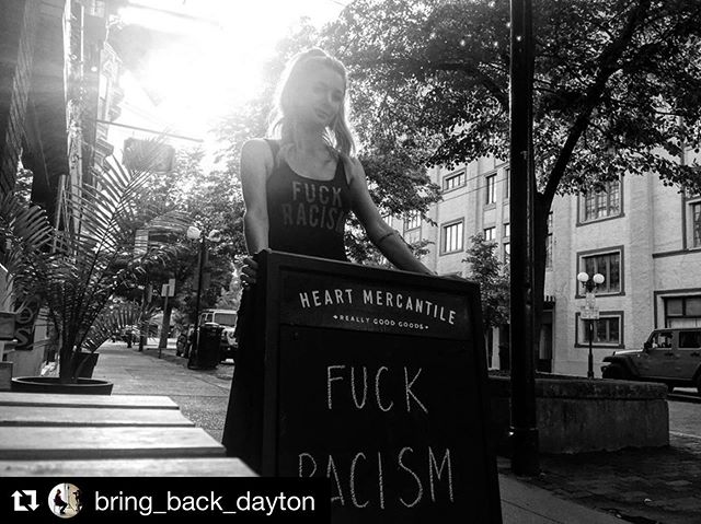 """#Repost @bring_back_dayton with @get_repost ・・・ May 23, 2019, Dayton, OH—Brittany, co-owner of the extremely popular Heart Mercantile, joins other Oregon District storefronts as Dayton mentally and physically prepares itself for the arrival of the KKK on Saturday, May 25. After receiving a permit from the city, this particular KKK chapter (hailing from Indiana), has been allowed to demonstrate in downtown's Courthouse Square. Currently, Dayton is in the long process of barricading safe zone areas and blocking city streets from car traffic and public transportation until Sunday, May 26. The general consensus/reaction from Dayton has centered around pop-up movements such as @unitedagainsthatedyt, with promoters like @heart_mercantile selling out of their newly minted """"Fuck Racism"""" tees in minutes. """"We sold out,"""" adds Brittany, as stands outside of her storefront, """"we've sold 70 in less than an hour, and now we're backordered. It's amazing. Unbelievable."""" Photo by: @bring_back_dayton  Subject: @heart_mercantile, 2019. #heart #heartmercantile #mercantile #store #dayton #daytonunitedagainsthate #unitedagainsthatedyt #ohio #fuckthekkk #endracism #fuckracism #bnw #localbusiness #business #storefront #goods #peace #protest #tshirt #girlgaze #photography #streetphotography"""