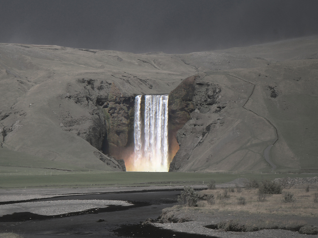 nobodyiswatchingus :     Waterfall amidst a mountain covered in ash after a volcano eruption.   Taken in Iceland. One of the most unique landscape photos I've ever seen.