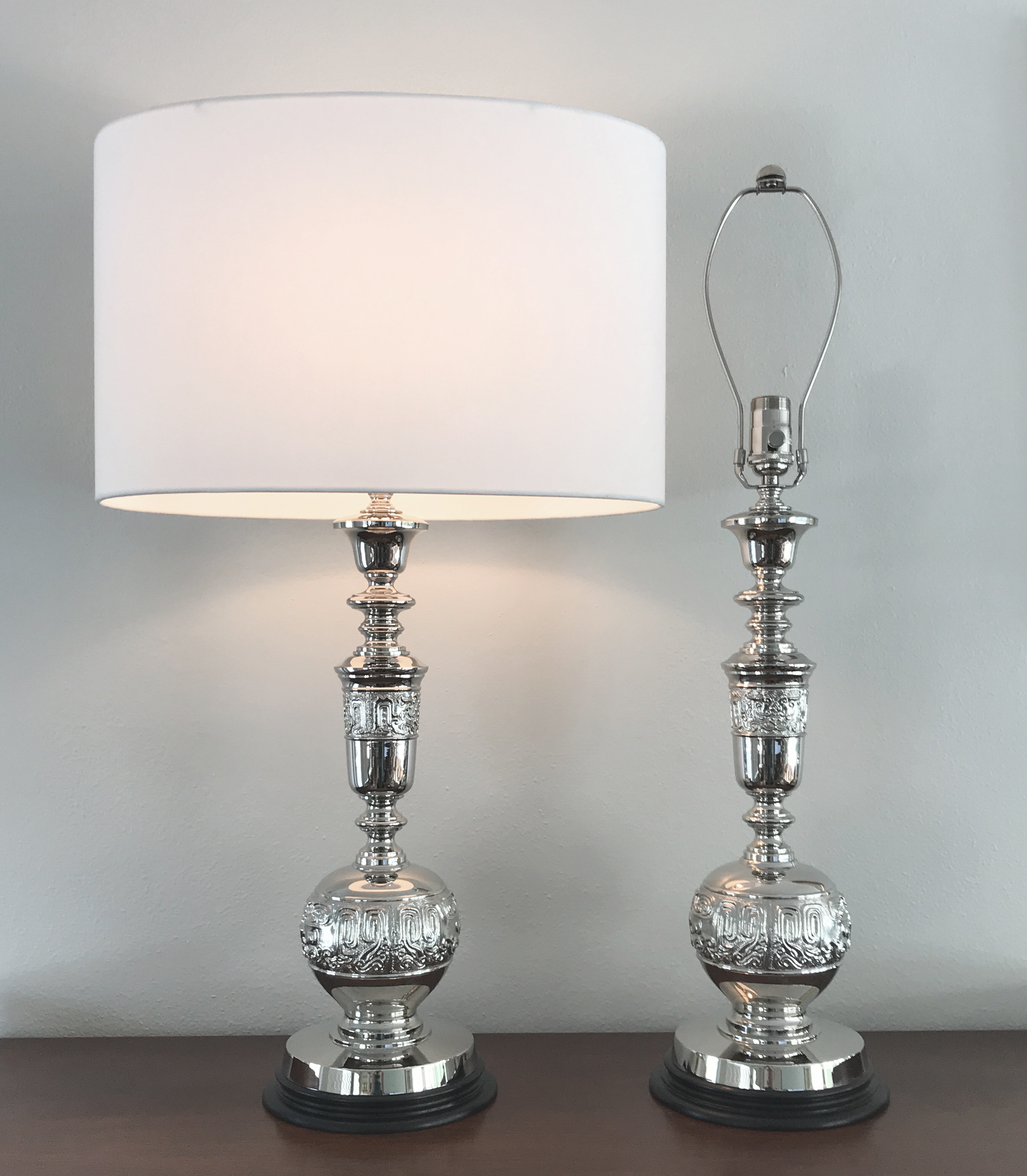 Polished Nickel Urn Table Lamps (pair)  Espresso stained wood bases with polished nickel plated cast brass bodies.  Full range dimmer on socket with black silk cord.  Shown with a white linen, oval shade.