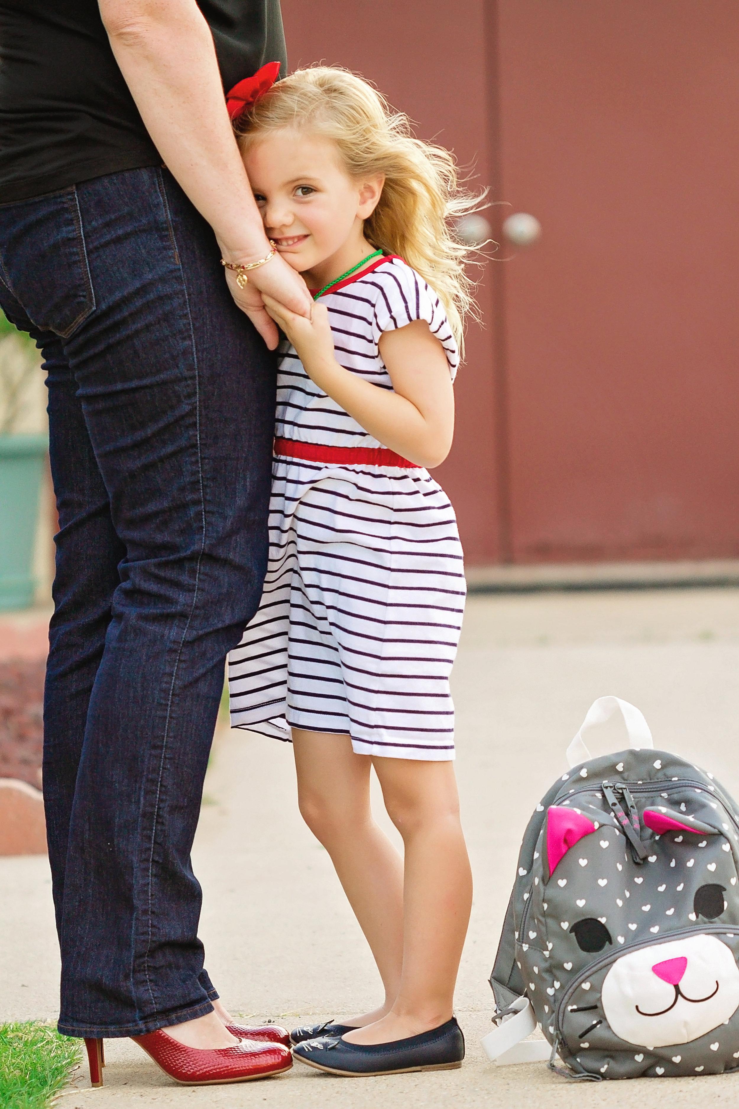 little girl leaning on mom with kitten backpack.jpg