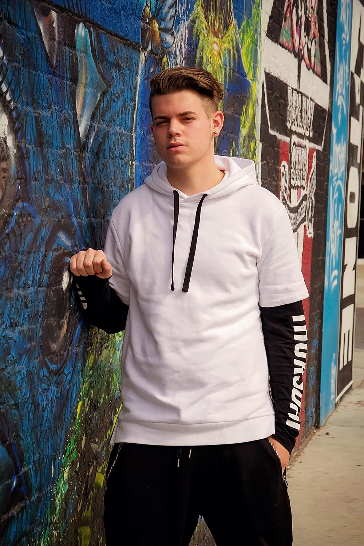guy in white against graffitti wall .jpg