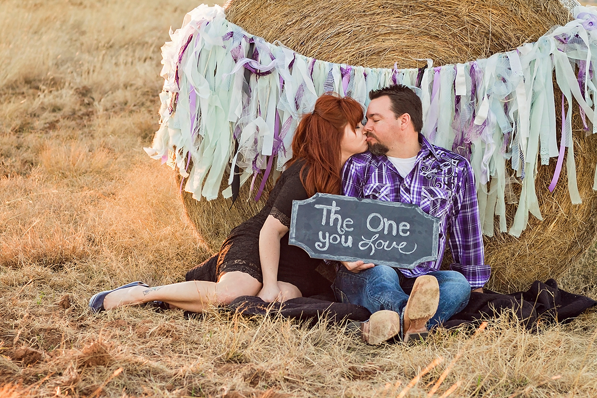 Couple in lace and plaid kissing by a haybale.jpg