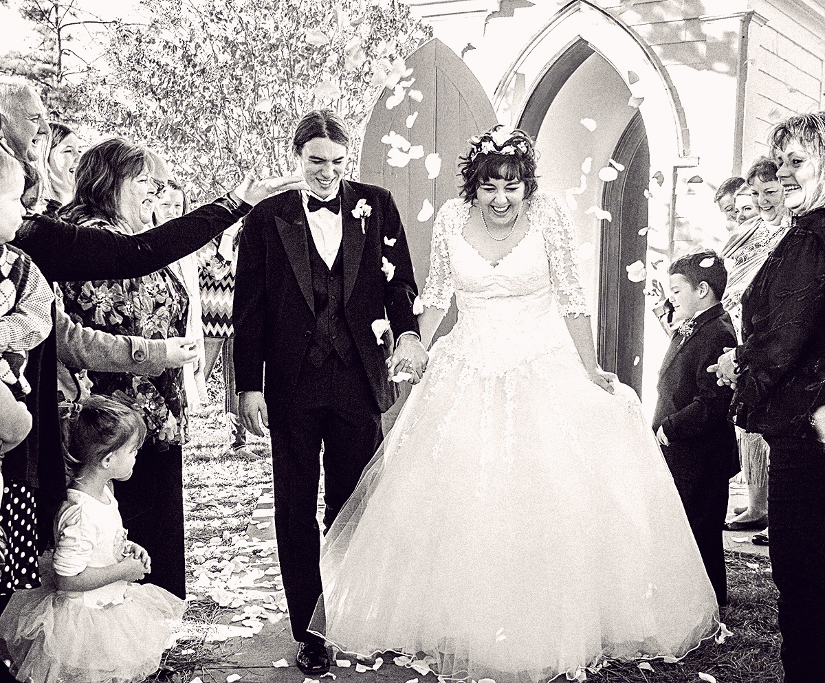 Wedding couple leaving the church while petals are being tossed.jpg