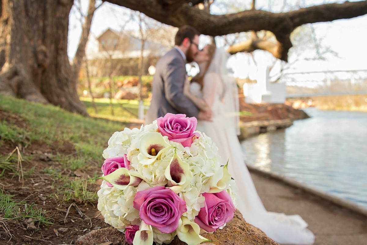 Bridal Bouquet with Bride and Groom kissing in background.jpg