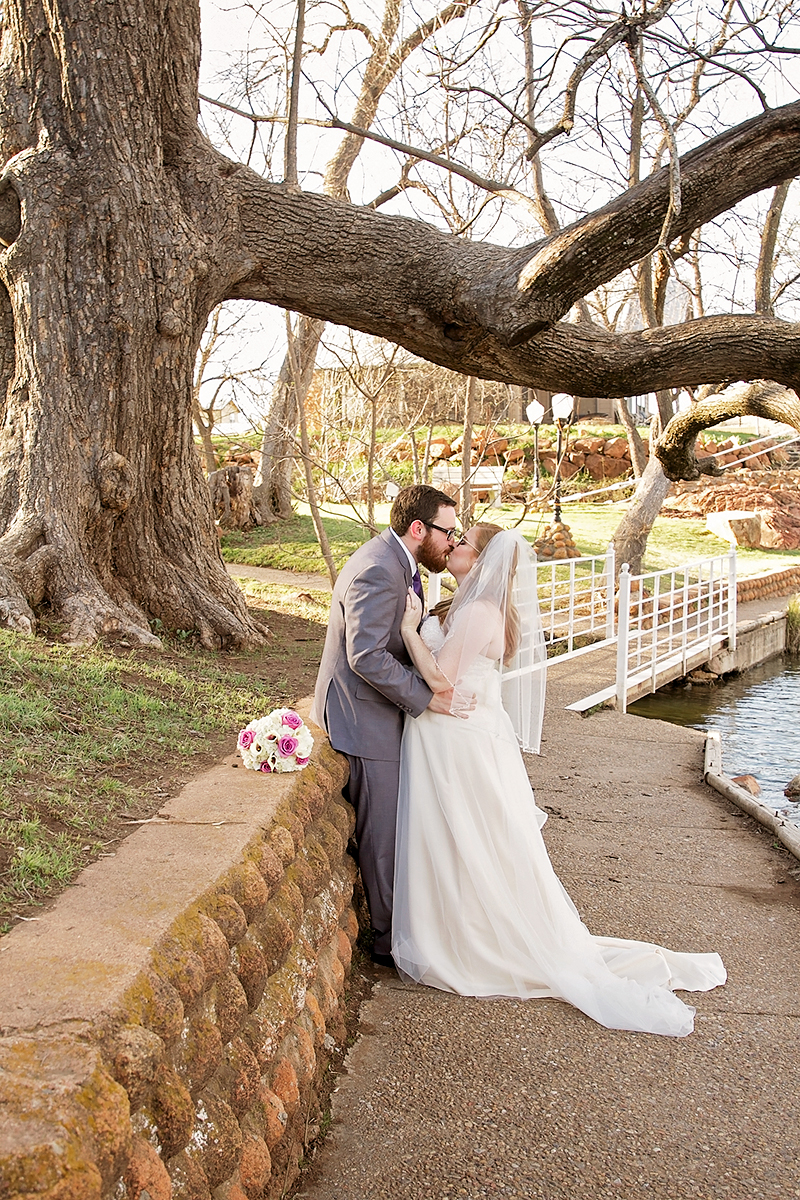 Bride and Groom Kissing under a tree in Medicine Park, ok.jpg