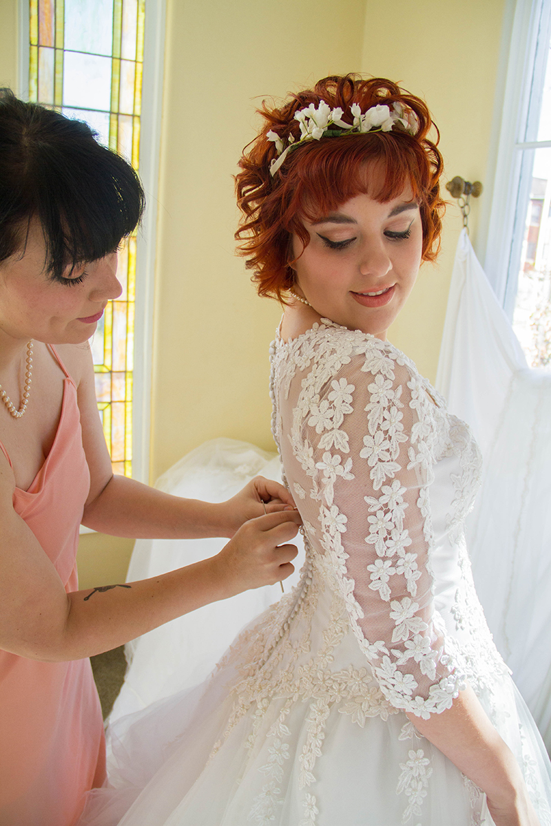 Vintage Bride getting dress buttoned by bridesmaid.jpg