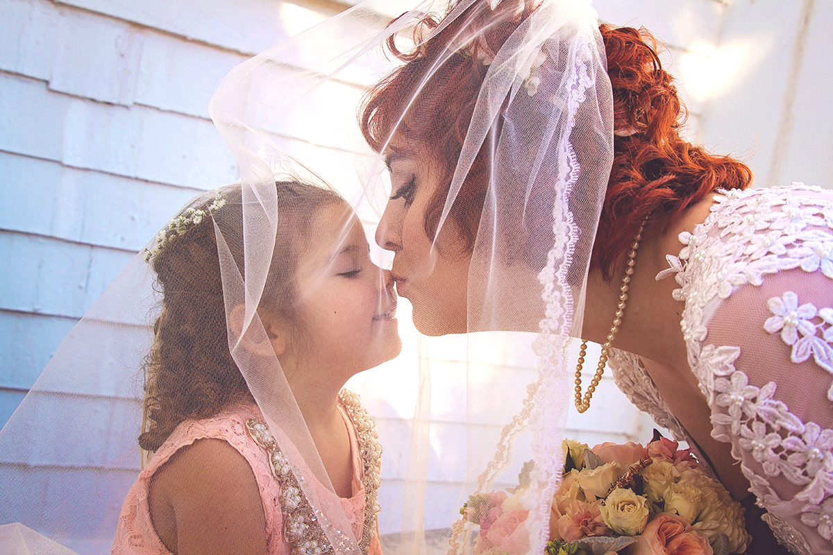 Bride kisses flower girl on nose under veil.jpg