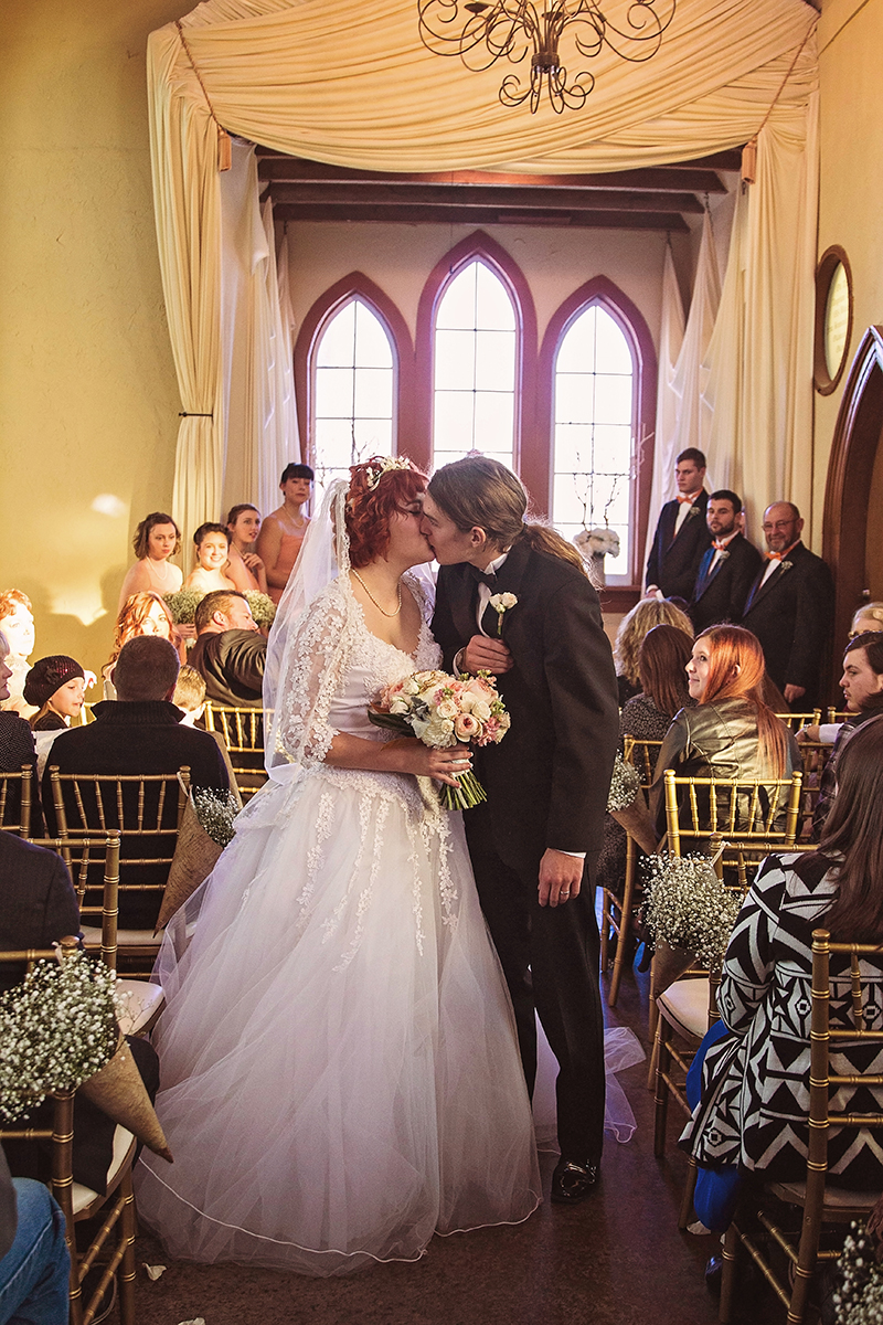 The mid aisle kiss of bride and groom.jpg