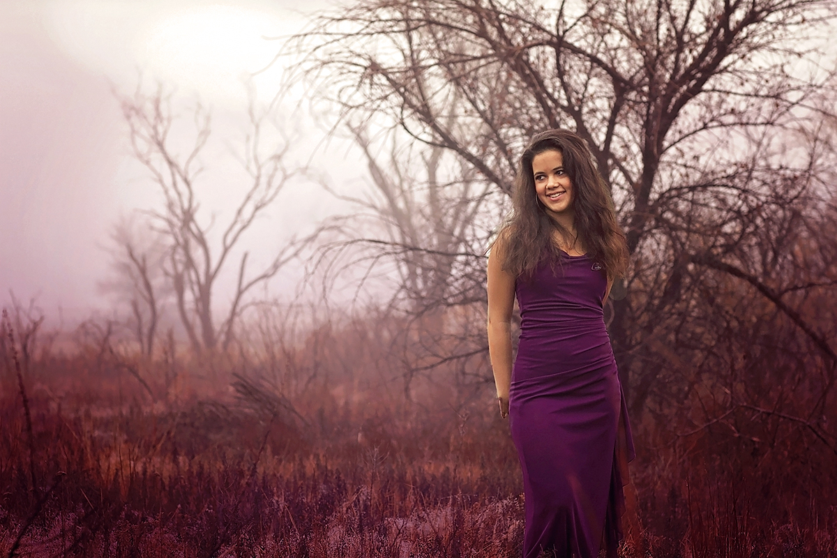 Senior Girl in purple dress standing in a field.jpg