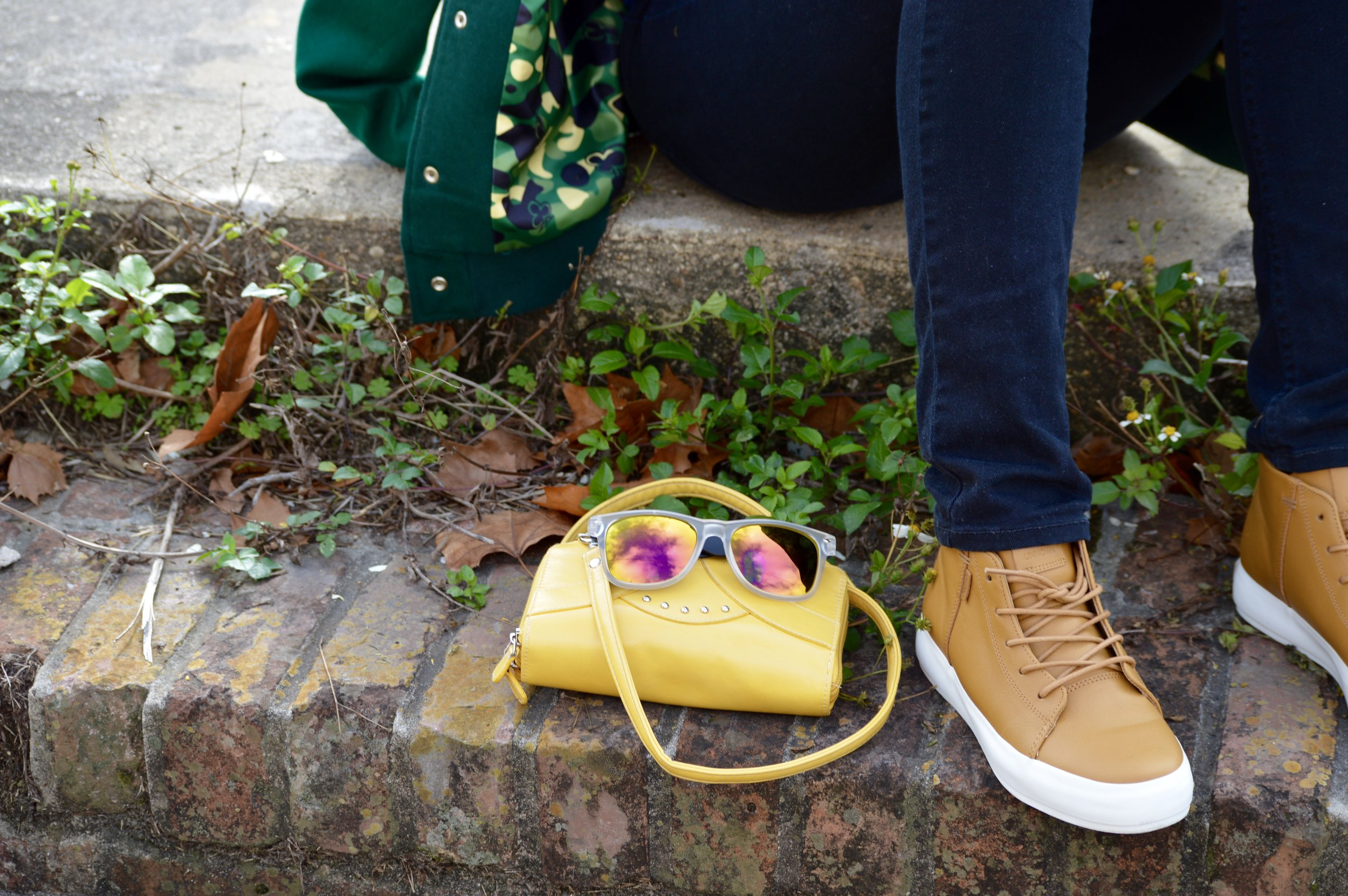 black distressed jeans brown leather sneakers yellow crossbody bag iridescent sunglasses
