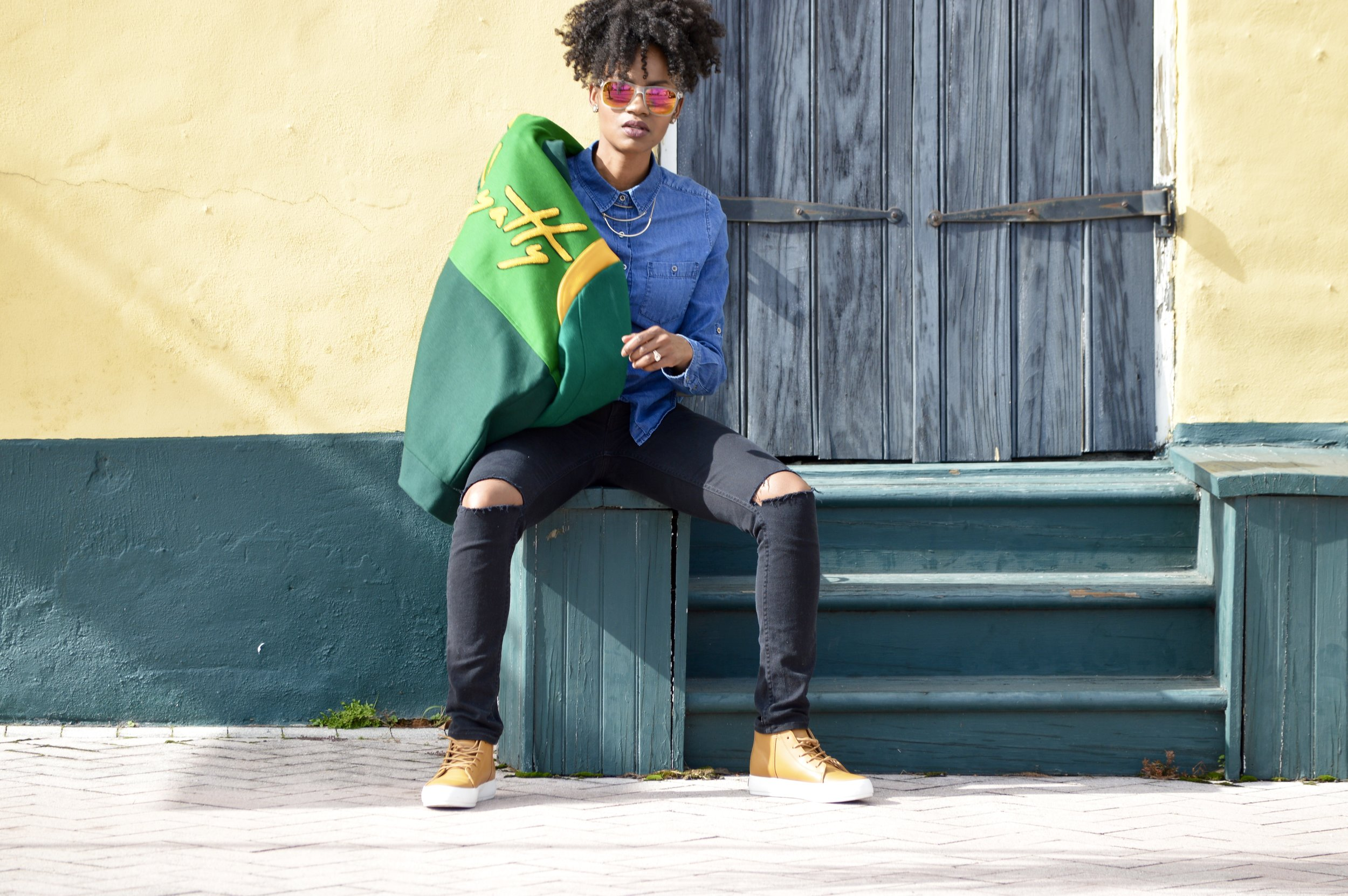 green and yellow varsity jacket denim button down shirt black distressed jeans brown leather sneakers