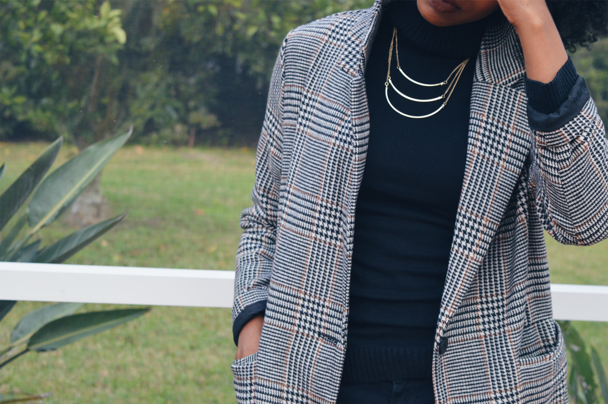 black turtleneck plaid trench coat layered gold necklace
