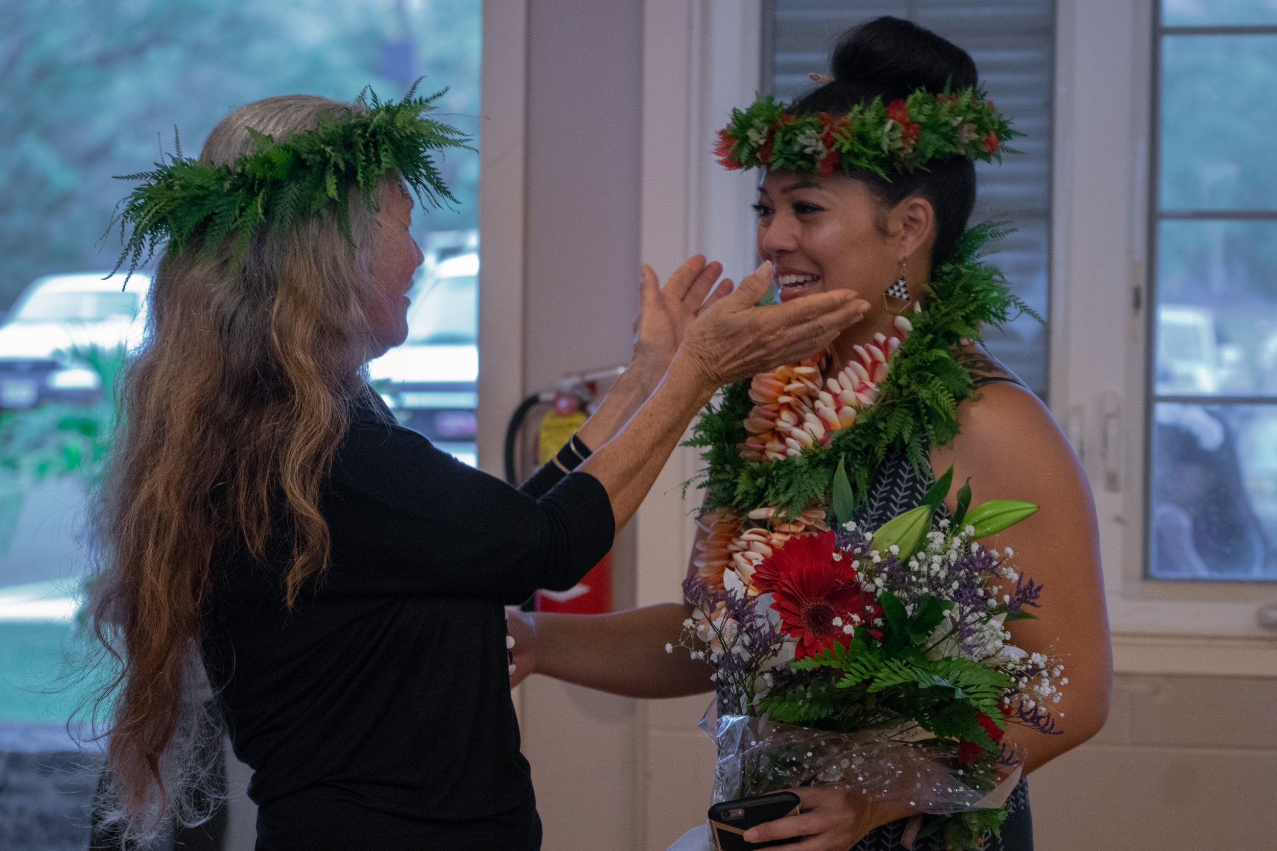 Native Hawaiian, Kanoelani Davis (right), is embraced by her kumu hula (hula instructor). Photo by Josiah Ching