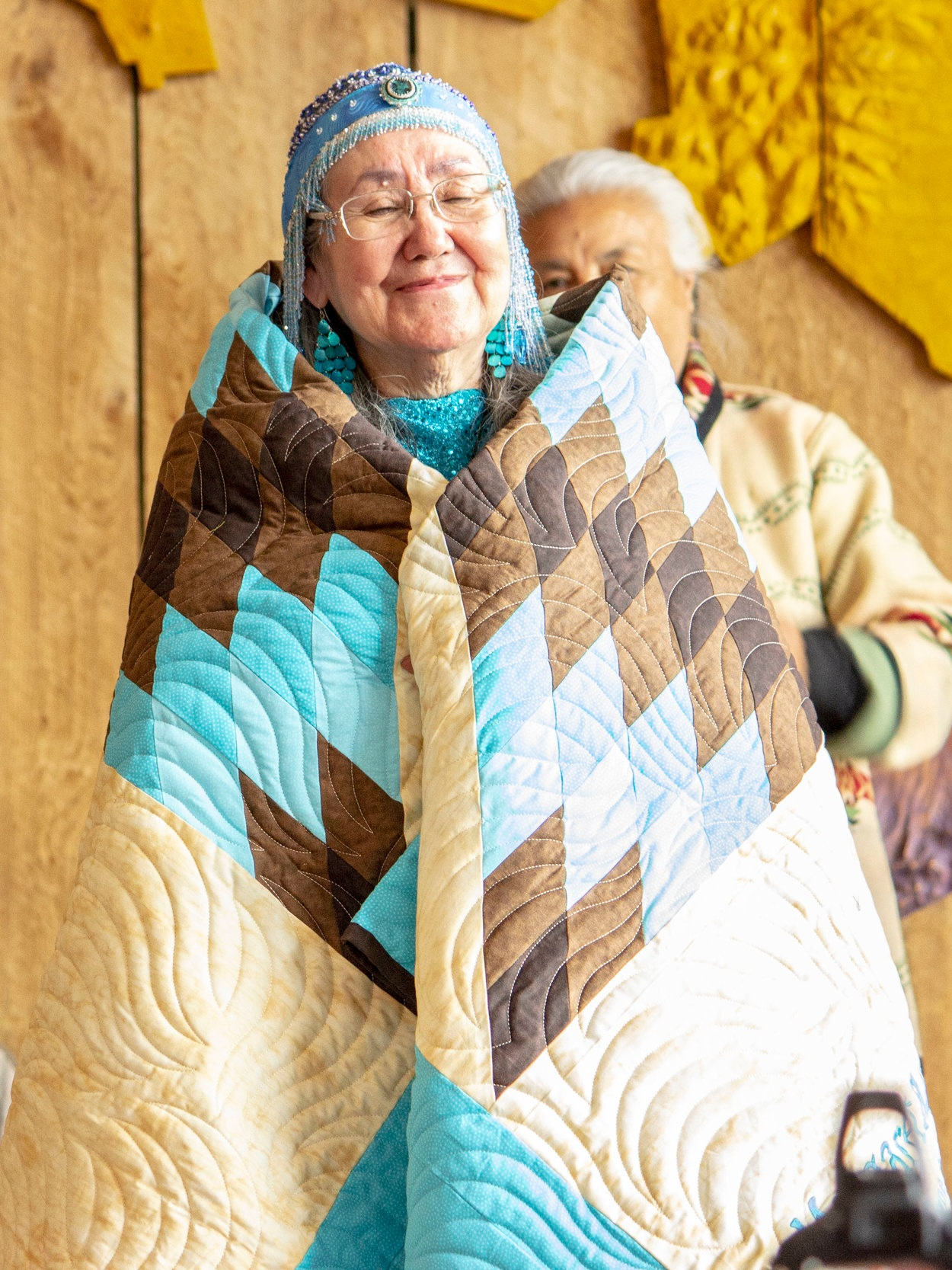 Margaret wrapped in her star quilt from FPF. Photo by Bryan Parker (Muscogee Creek/Mississippi Choctaw).