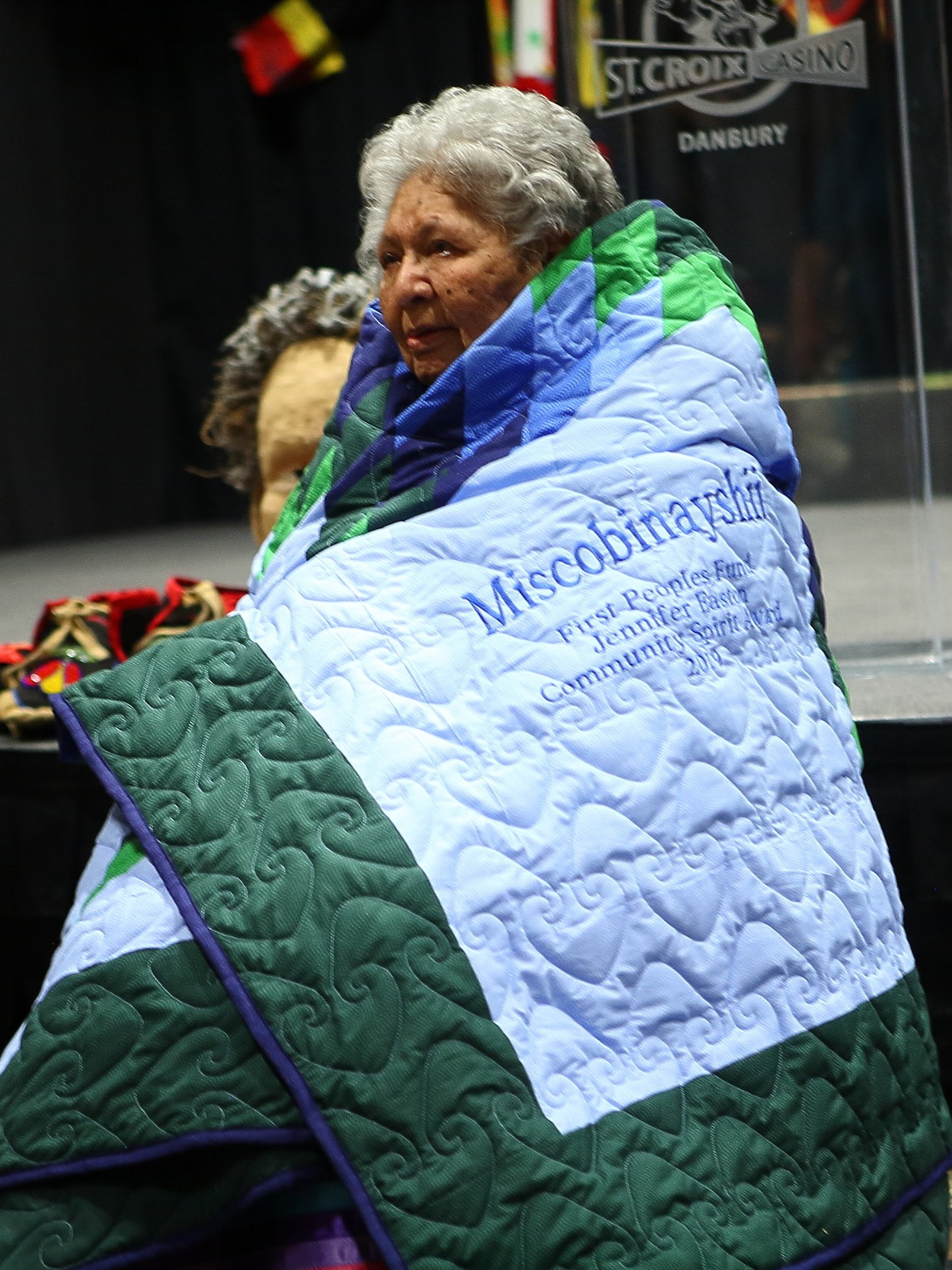 Miscobinayshii wrapped in her star quilt from FPF. Photo by Falls Portrait Art Studio.