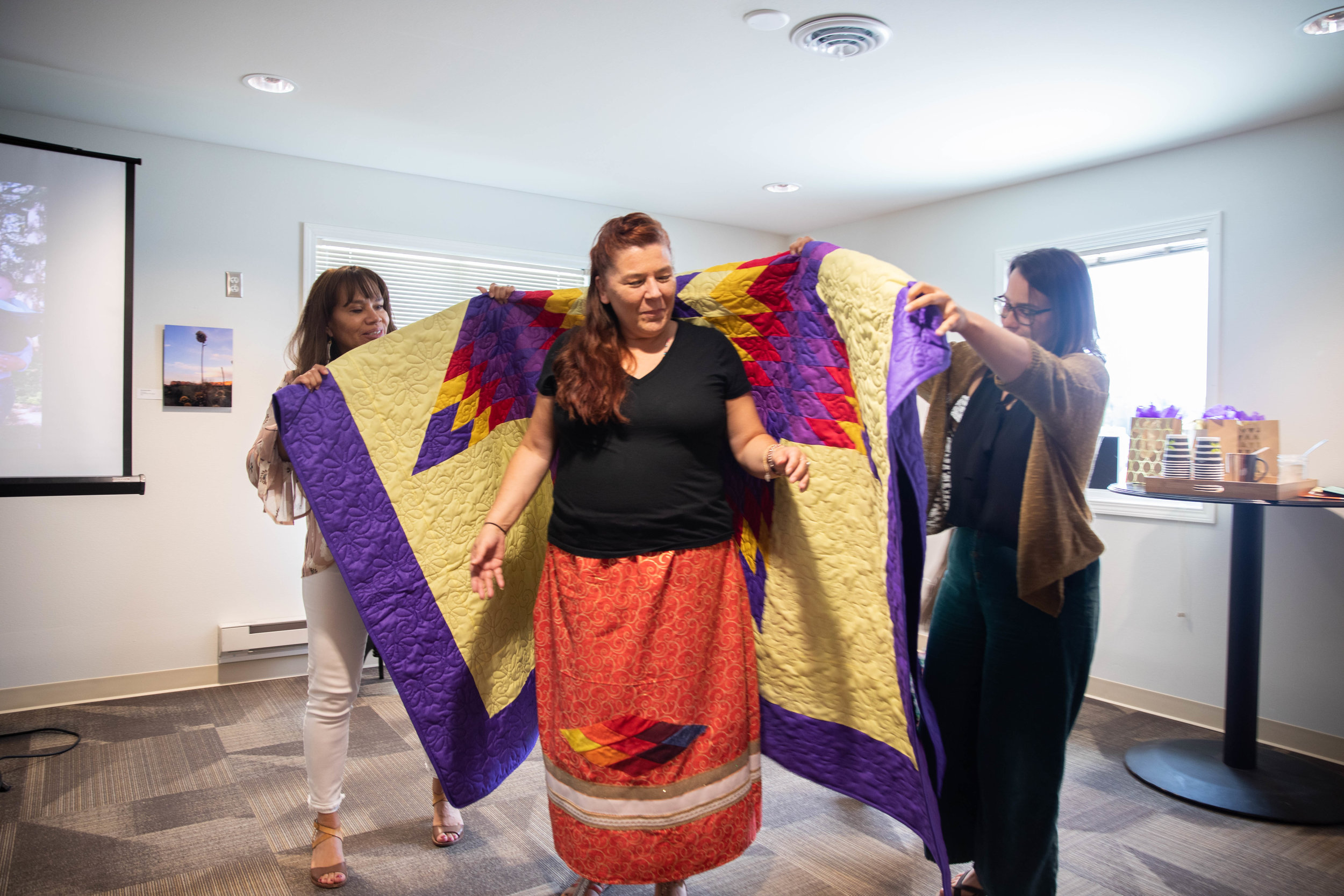 FPF President, Lori Pourier (Oglala Lakota) and FPF Fellowship Program Manager, Amber Hoy, wrap Melissa in a star quilt.  Photo by Roxanne Best (Confederated Tribes of the Colville Reservation).
