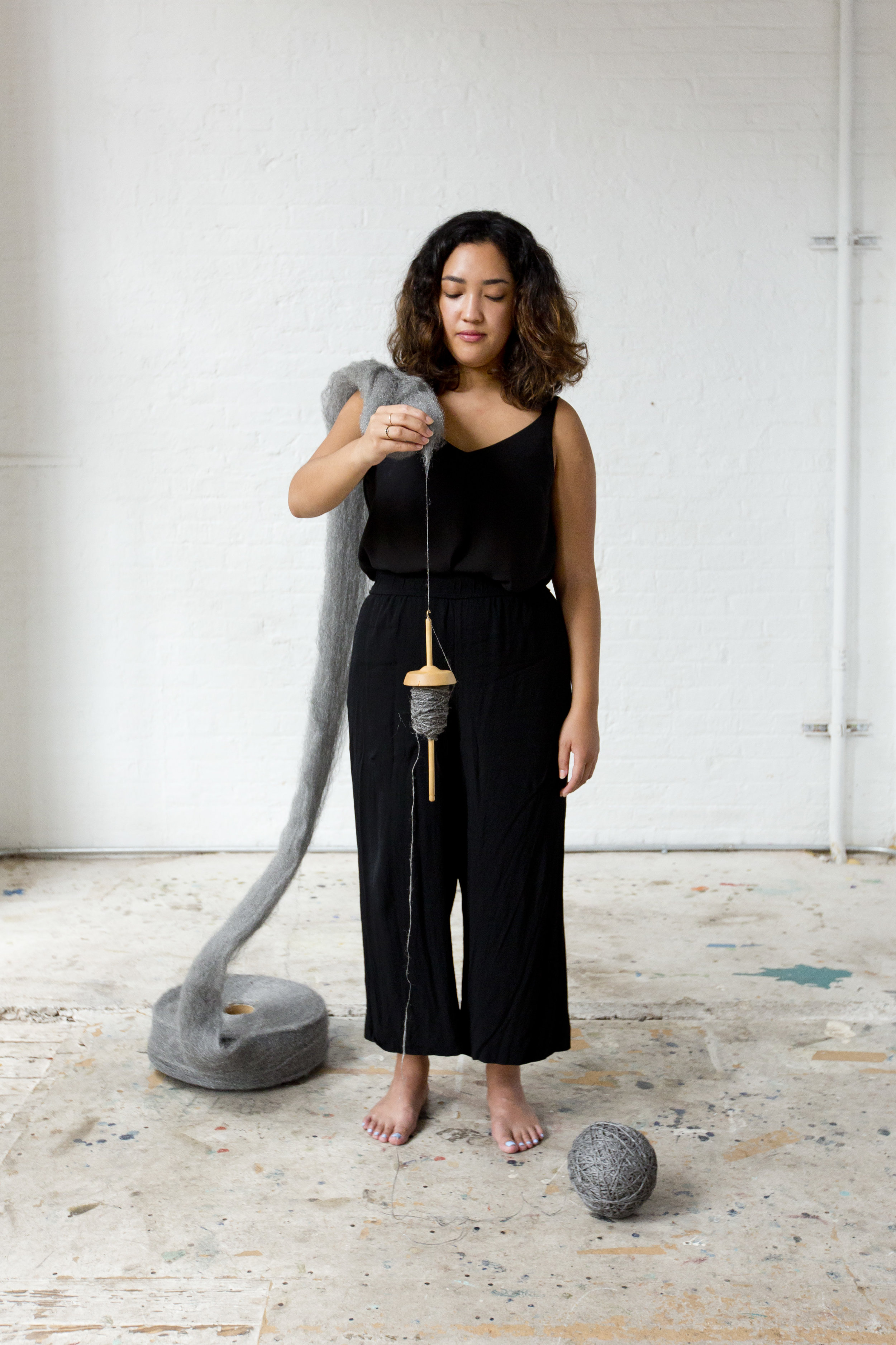 Image of Christina Crisostomo holding a drop spindle to showcase the process of spinning steel wool into yarn.