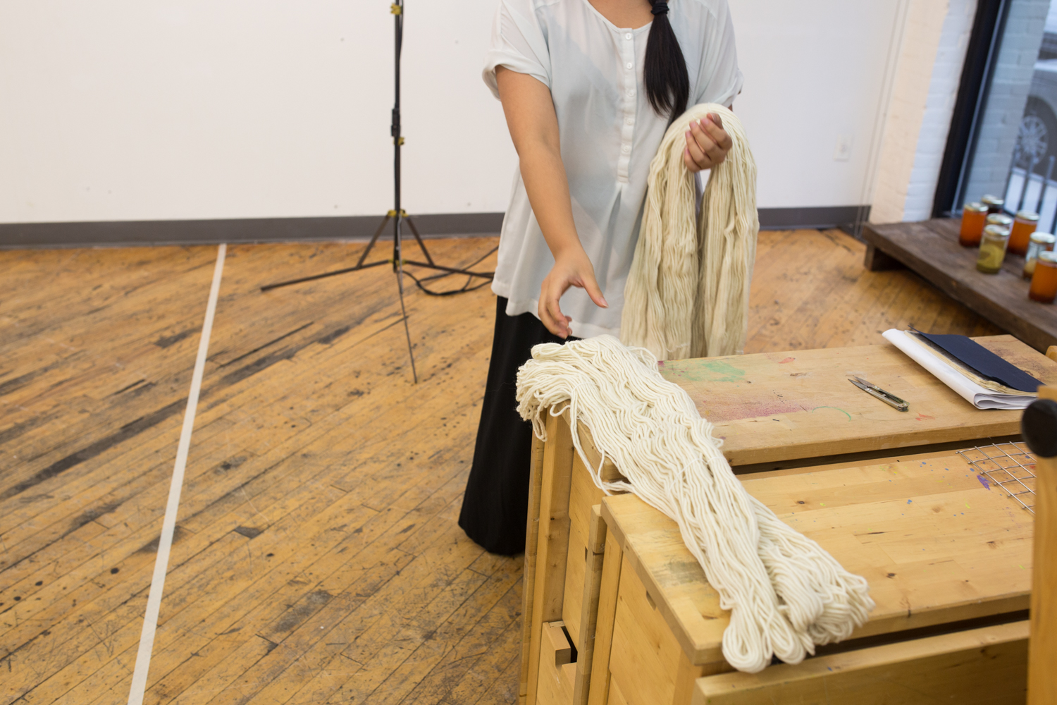 Images will go in sequence of the performance. Here is the very beginning where the artist is picking up skeins of white yarn from the table. She's wearing a white top and black full-length skirt. Her hair is in braids.