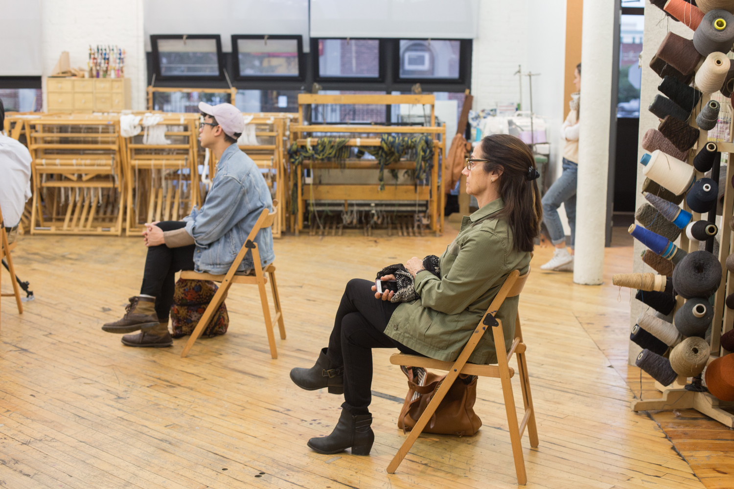 Two audience members watching the performance. Cones of yarn and weaving looms are in the background.