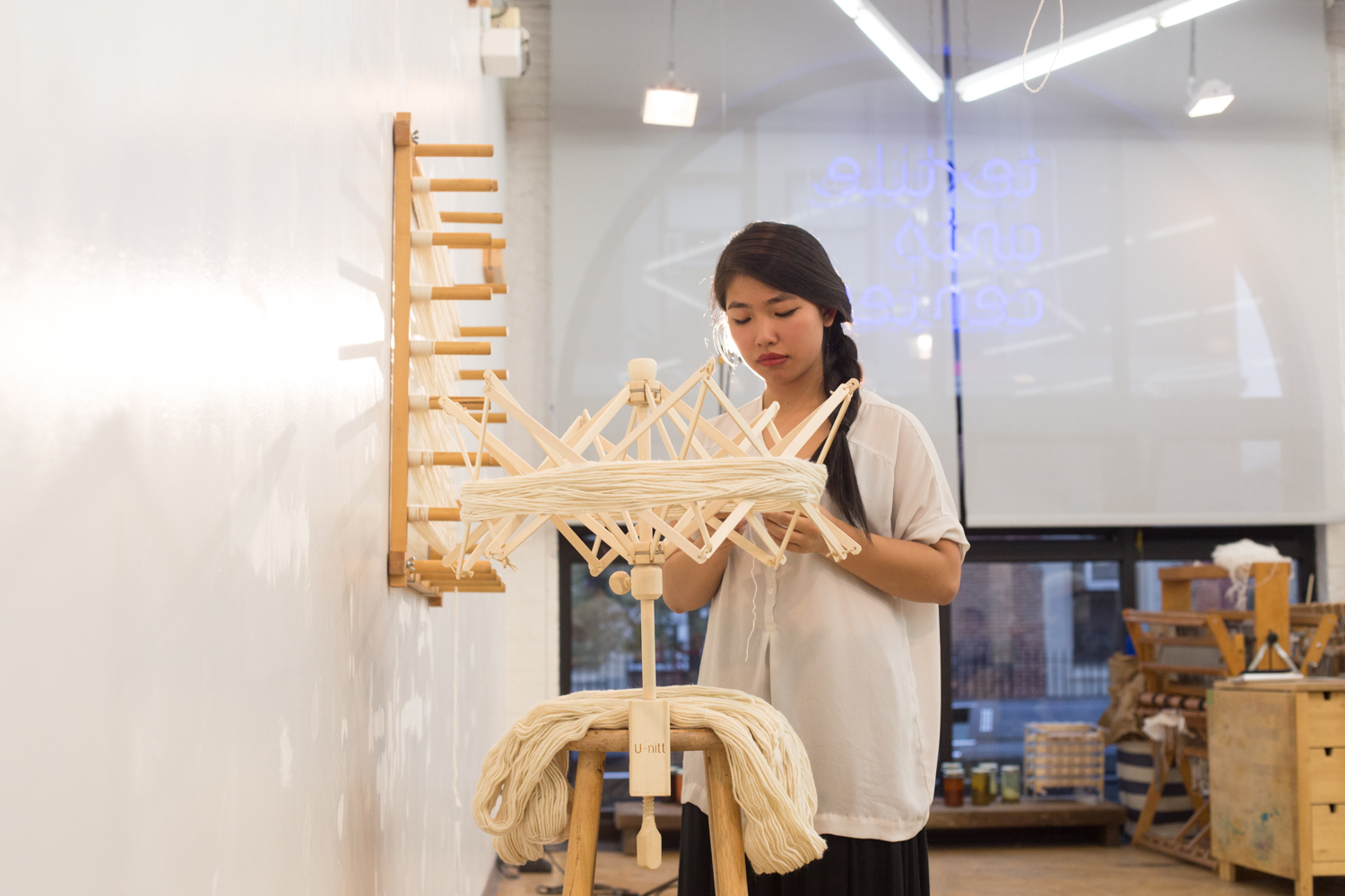 Side view of the artist behind the swift, also known as a yarn winder.