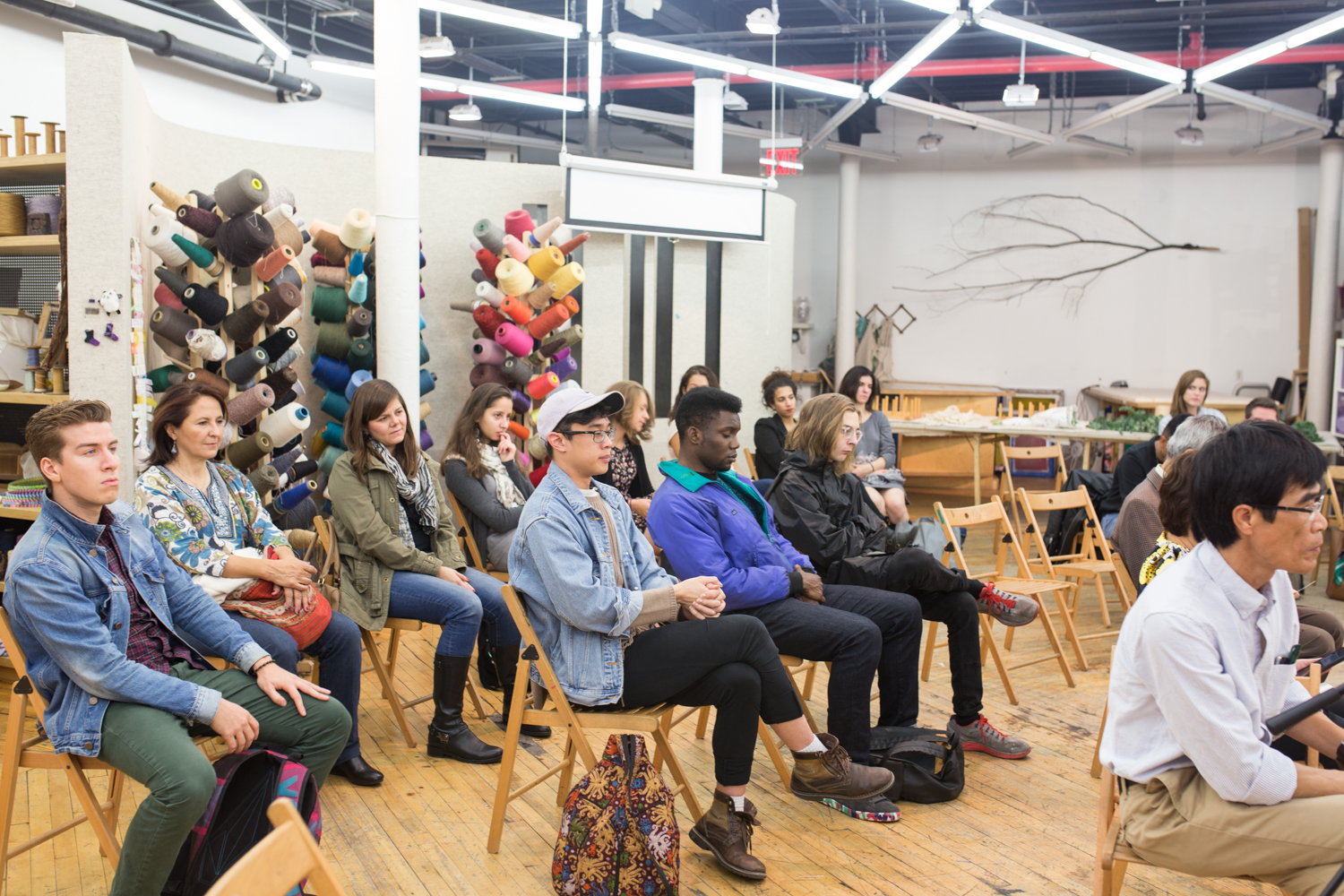 The room is filled with audience members as they watch the performance intently.