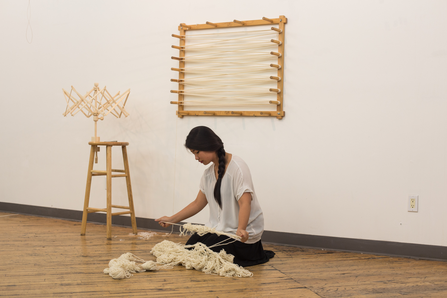 The artist is on the floor stretching the heap of yarn to create knots.