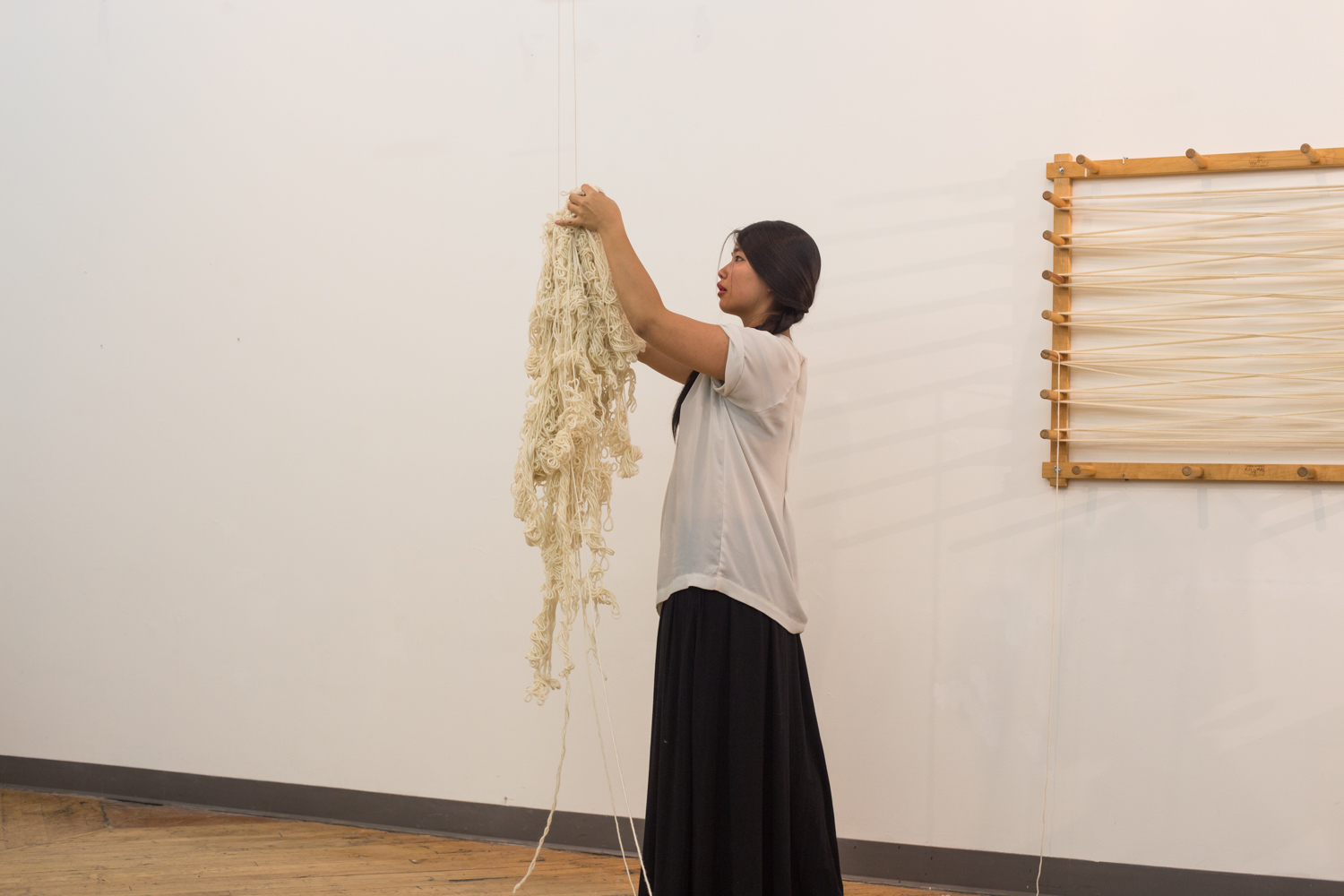 The artist lifts her hand to untangle a knot at the top of the suspended yarn, which is the same height as she is.