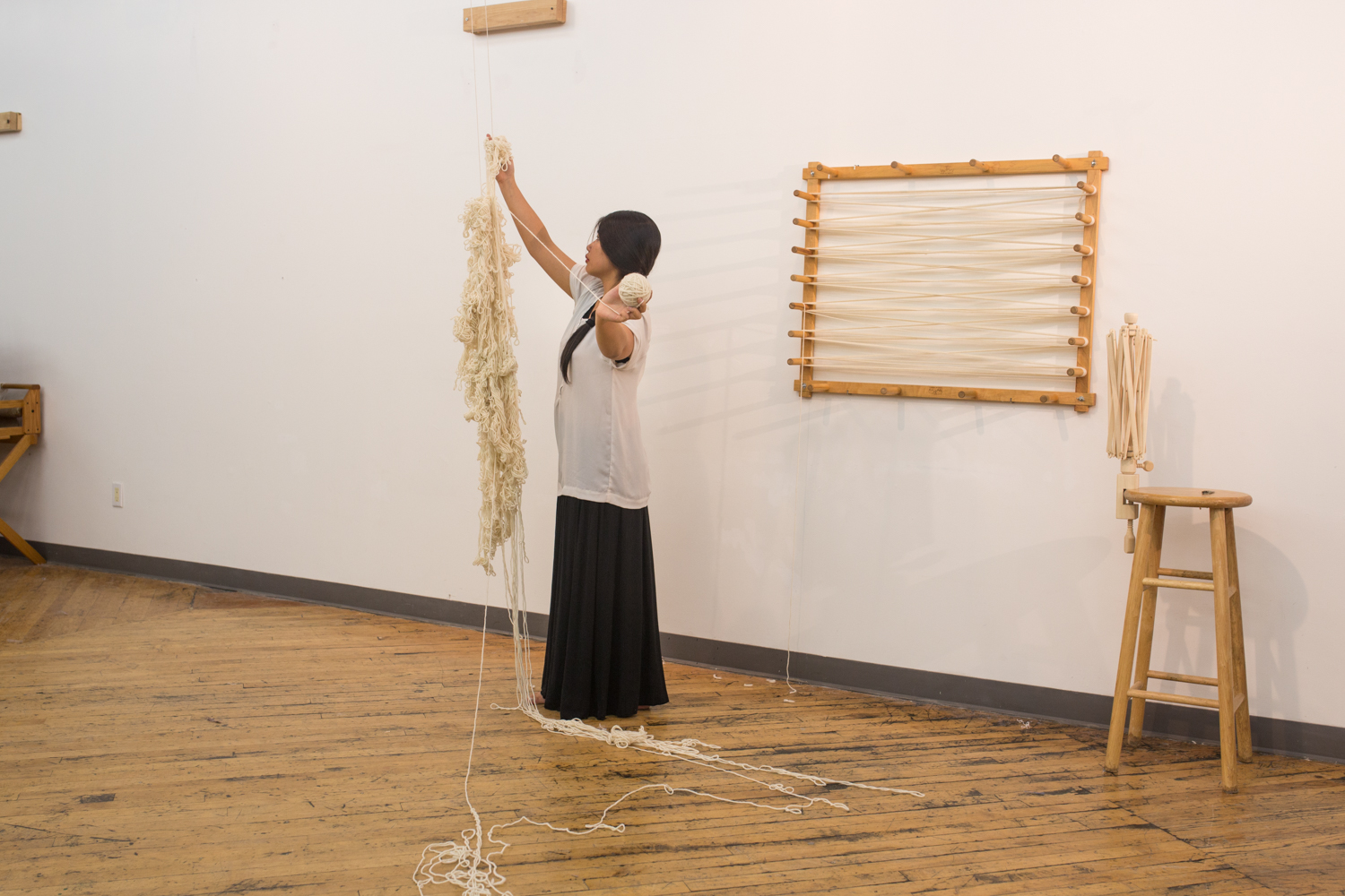 The artist holds a ball of yarn (around 1 inch in diameter) that she has untangled in her left hand as she continues to unravel with her right hand. Three-fourth of the knotted yarn has been unraveled.