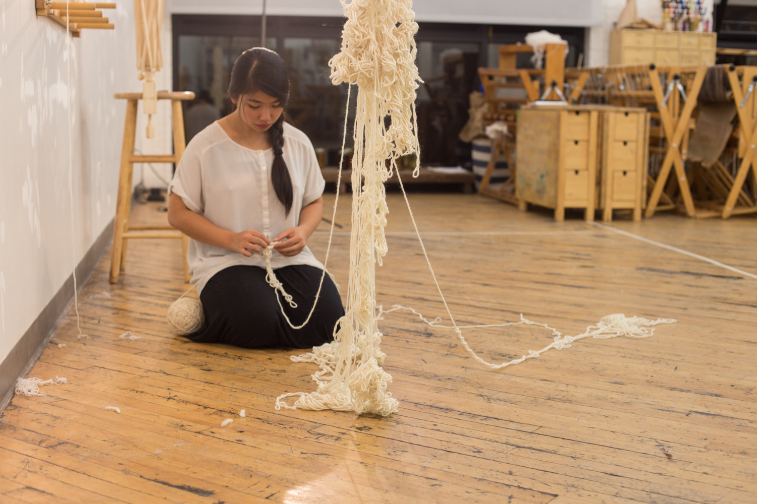 The artist focuses on untying a knot as she kneels on the floor with the ball of untangled yarn (still at 3.5 inches in diameter) next to her foot.