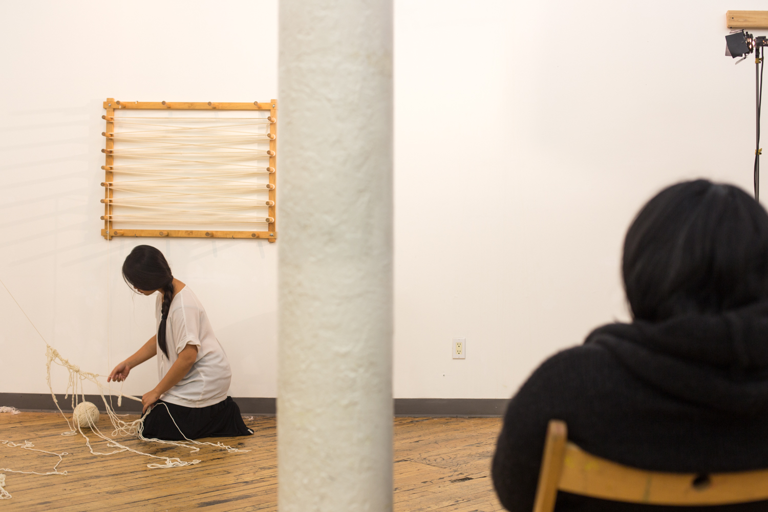 The image is split in the middle by a pole. On the left side is the artist kneels on the floor untangling and the right side is of an audience member.