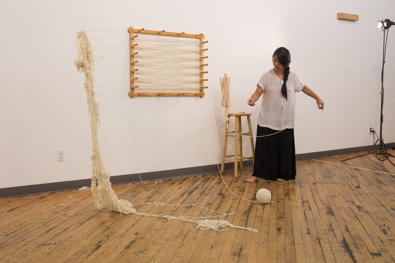 The artist is standing and unraveling. The ball of untangled yarn is now at 4.5 inches in diameter. Half of the knotted yarn has been untangled while the rest cascades from mid-air to the floor.