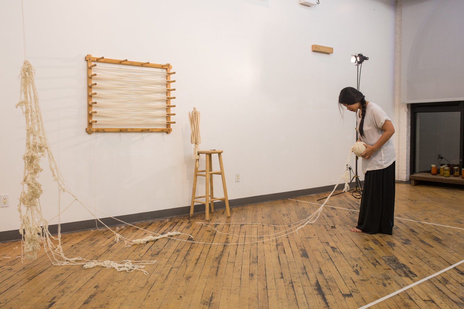 The artist stands far away from the suspended/knotted yarn as she wraps the untangled portion onto the ball of yarn (around 5 inches in diameter) in her hand.