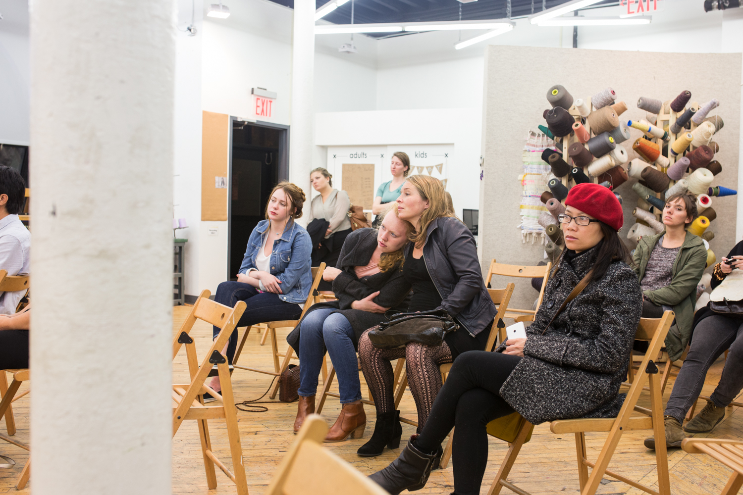 A different group of the audience watches the performance. Two women are leaning onto each other as they hold hands.