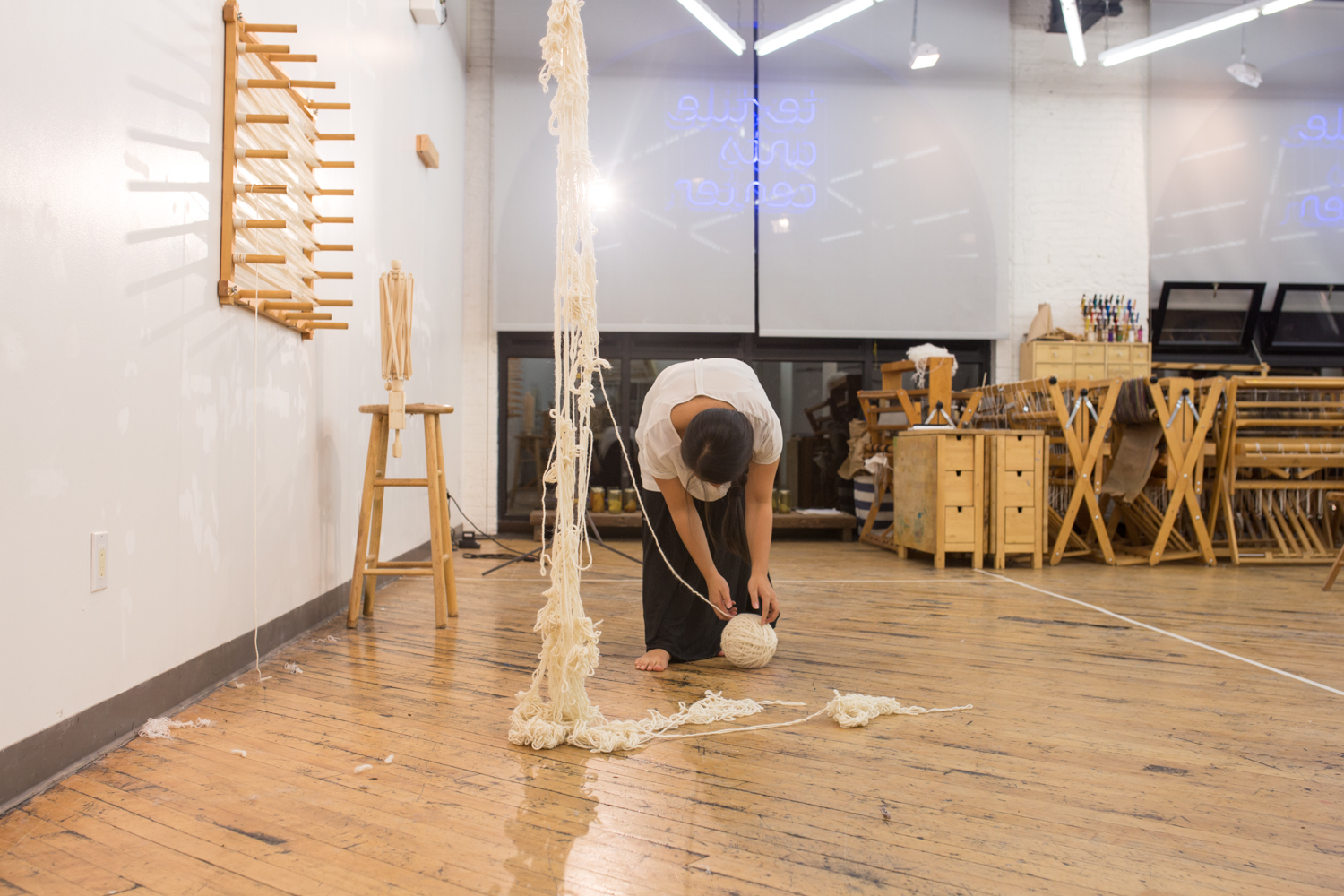The artist is placing the ball of untangled yarn onto the floor. It's now at 6 inches in diameter.