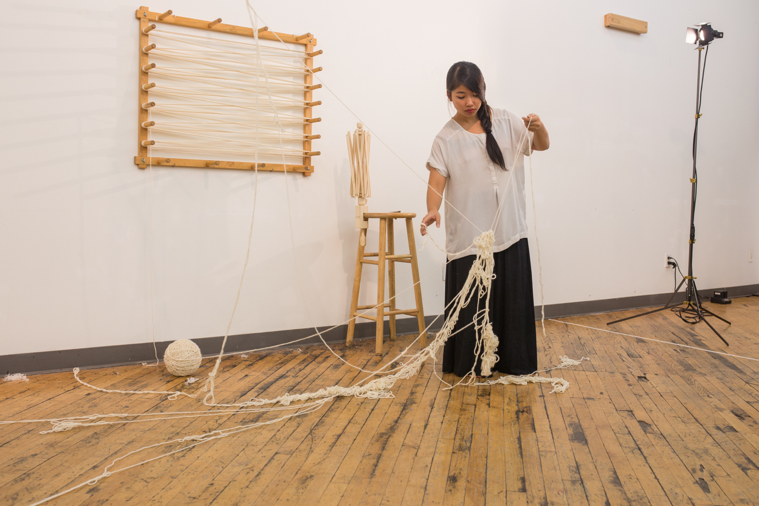 Only one strand of knotted yarn is suspended in the air while the rest is on the floor.