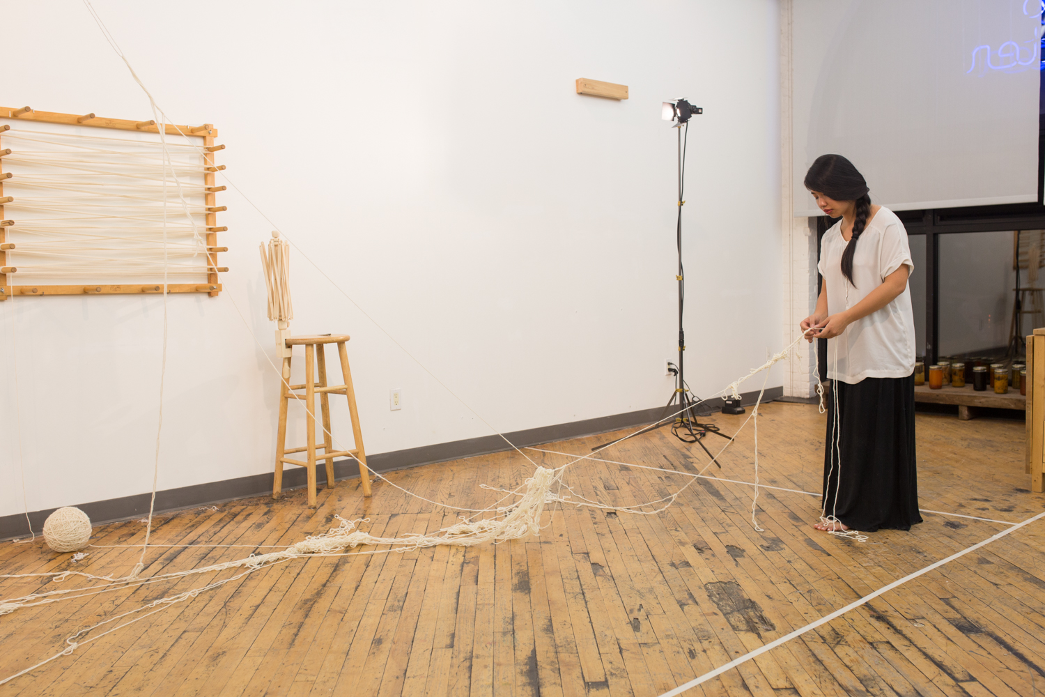 The artist uses the one strand of suspended, knotted yarn as an anchor to untangle the rest of the heap of yarn. The ball of untangled yarn is on the side.