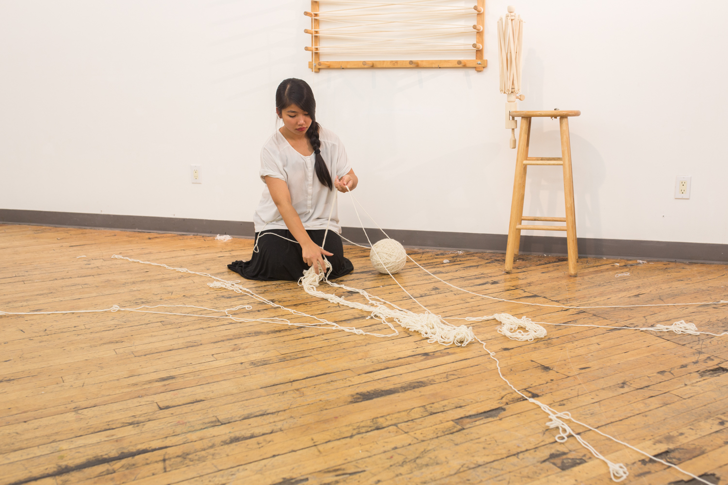 The artist is on the floor. The rest  of the knotted yarn (a very small amount) is now on the floor. The ball of untangled yarn is now at 7.5 inches in diameter.