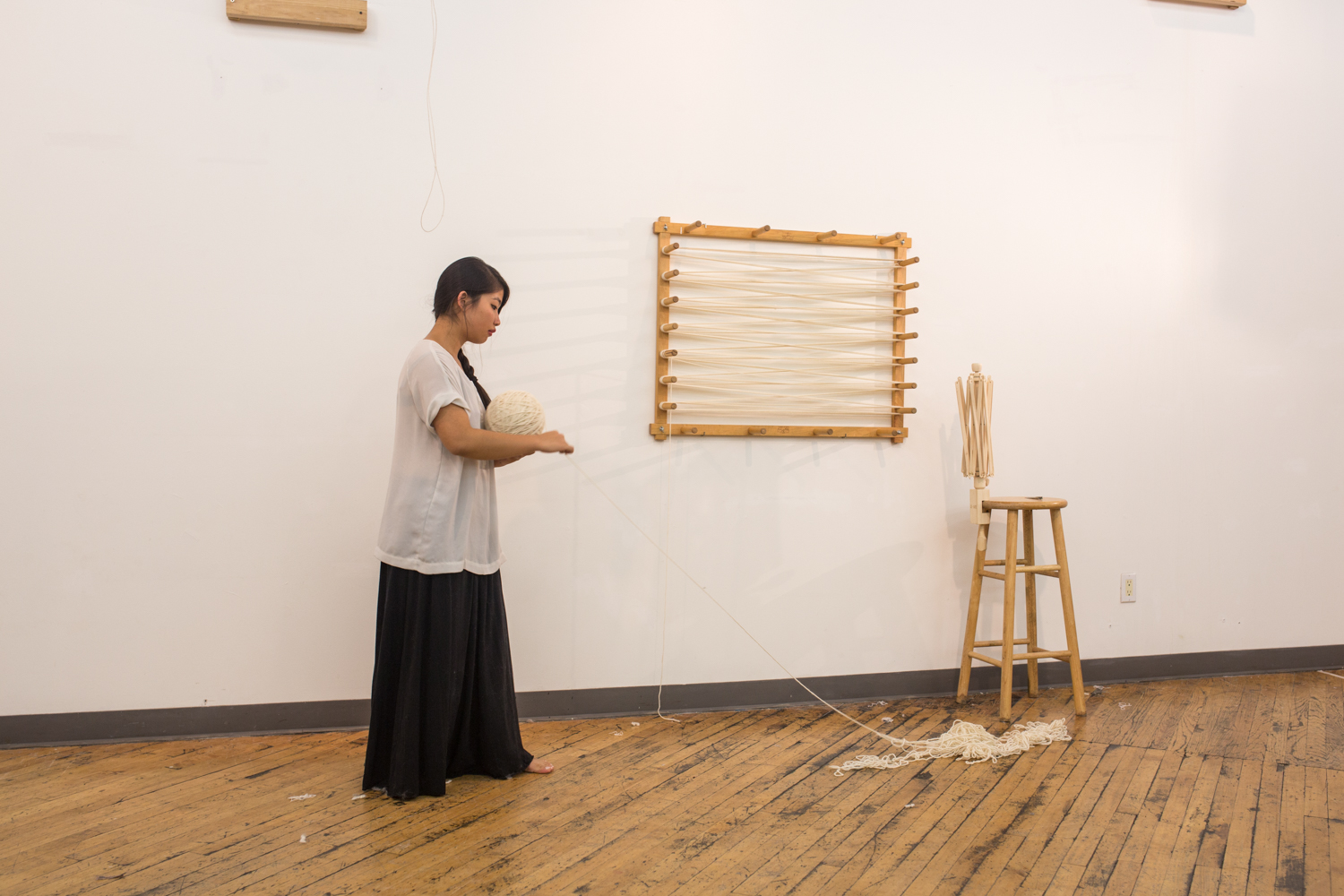 The artist wraps the untangled yarn onto the ball in her hand. Only a small amount of knotted yarn is left.
