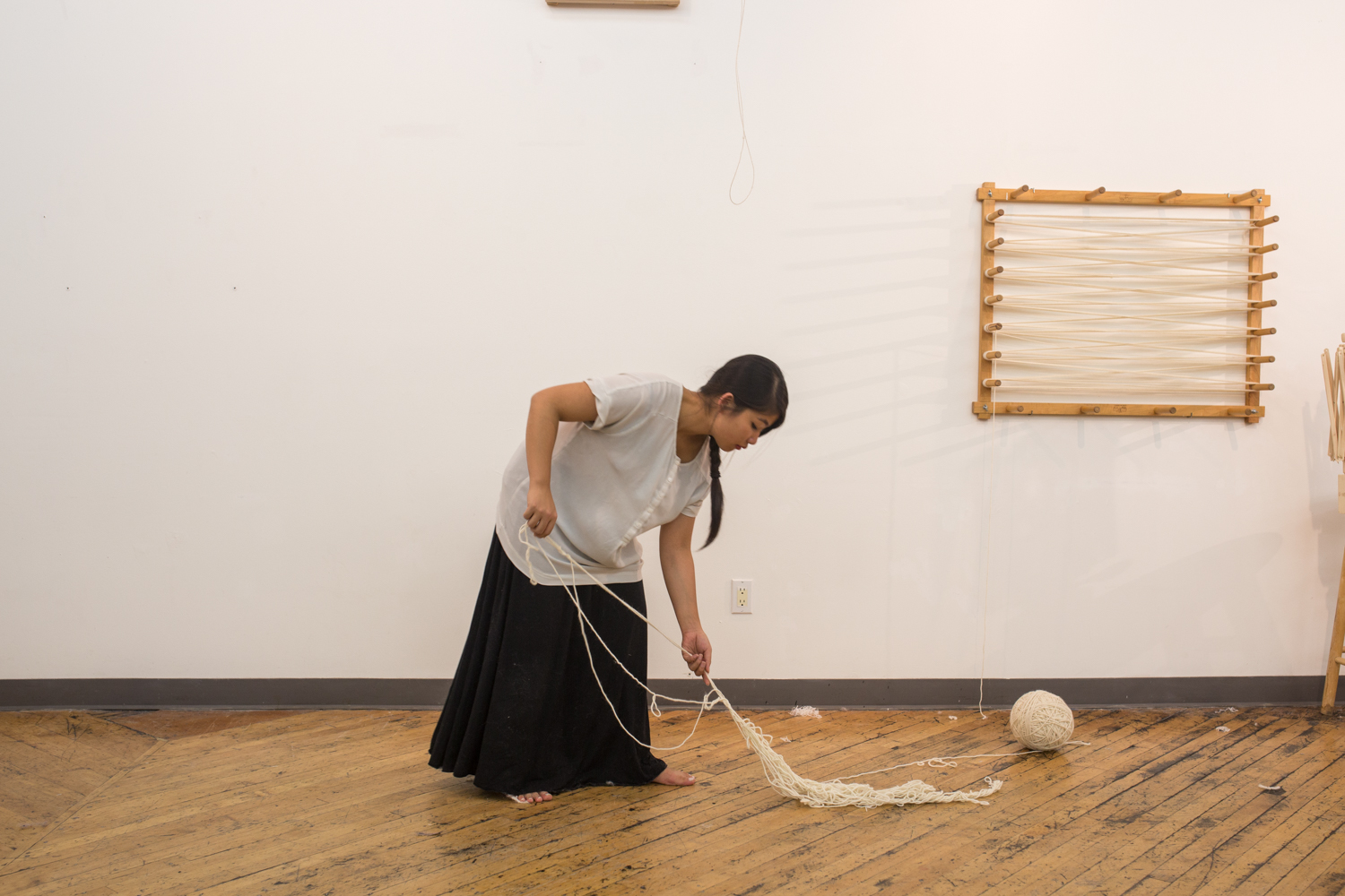 The artist bends down the untangle a knot.