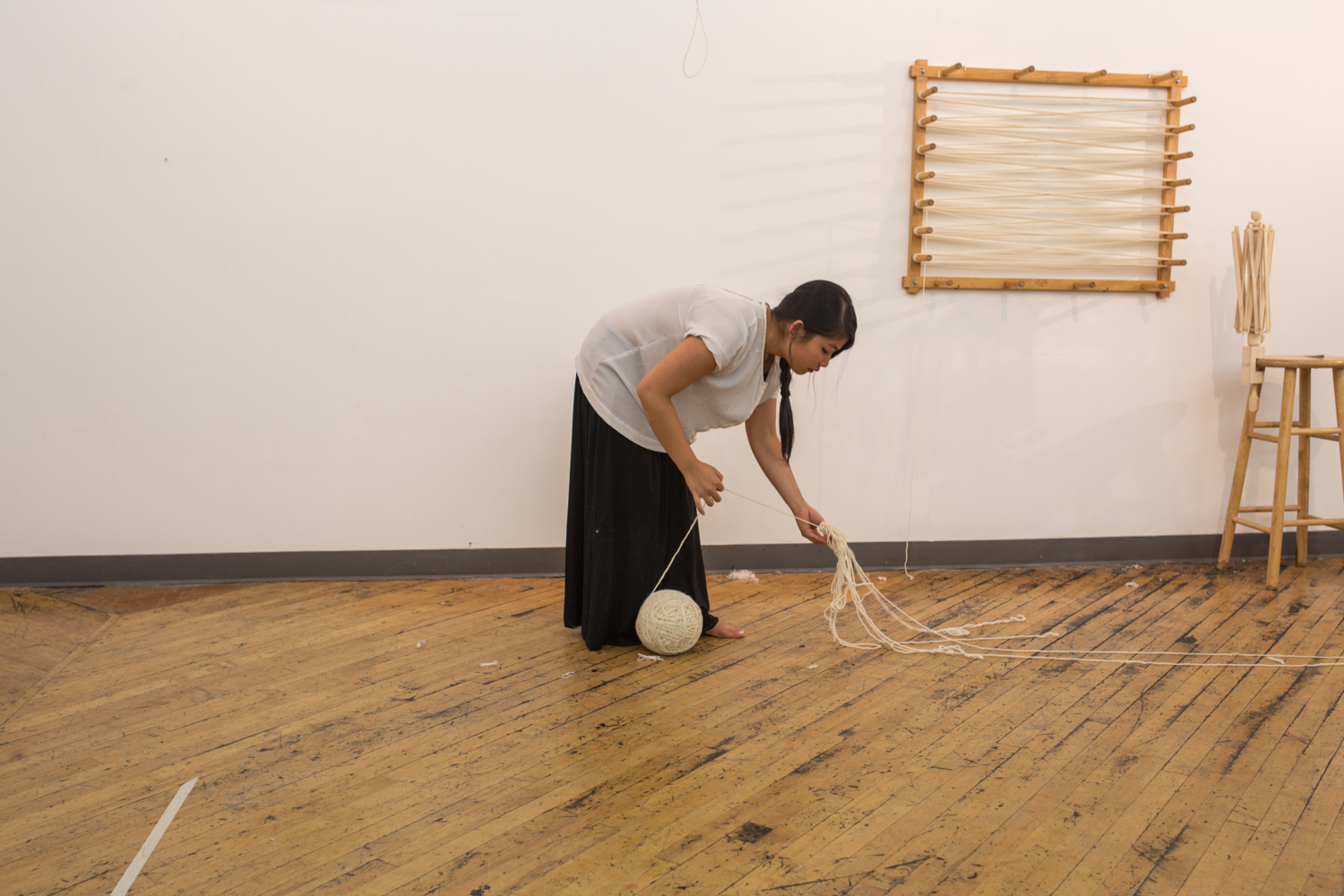 The artist bends down and focuses on a knot.