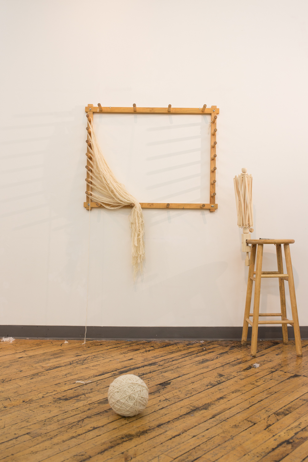 The performance ends with all the yarn being untangled. The last shot is a still life of the warping board, the stool and swift, and the ball of untangled yarn.