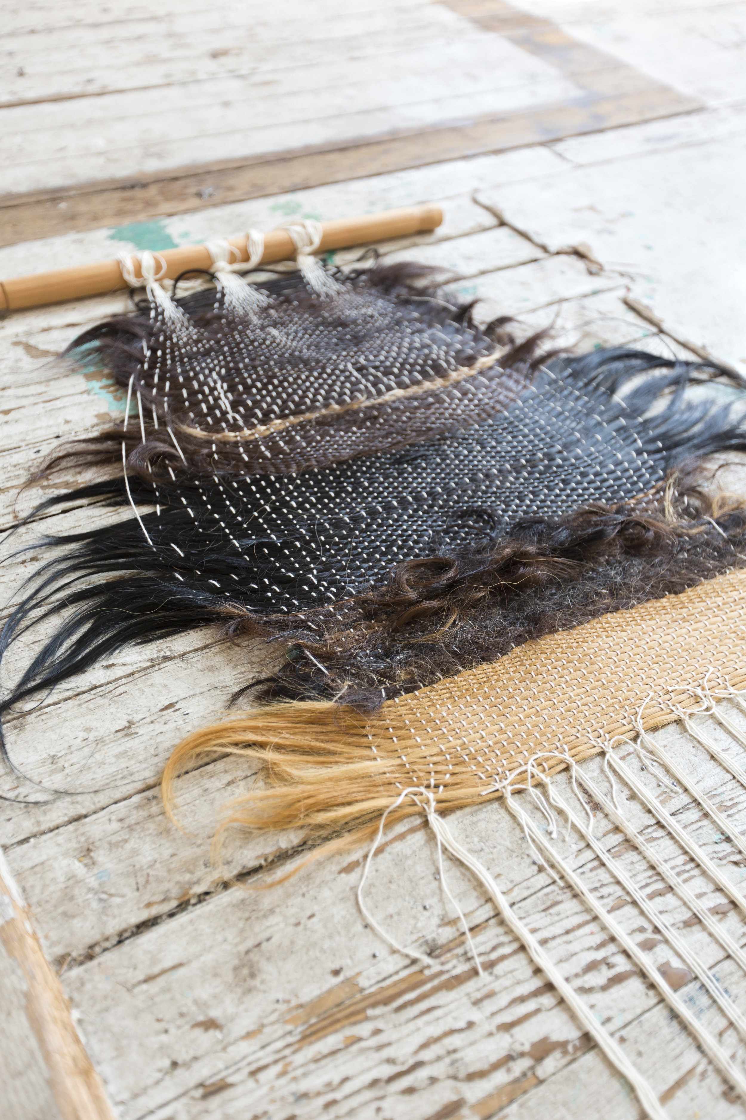 The hair weaving lays flat on the floor with the wooden beam at the top. Hair are woven in horizontally with the white color of the warp threads showing through. Hair color ranges from pitch black to brown to blonde. Most of the hair is straight with an one-inch stripe of curly and hand-spun short hair.