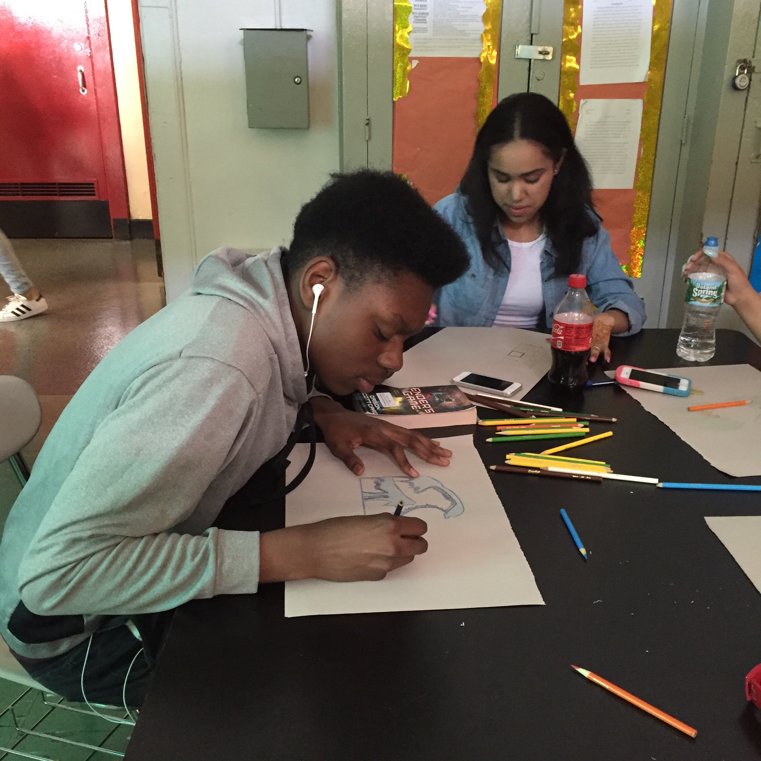 Students using color pencils to sketch out their quilt piece.