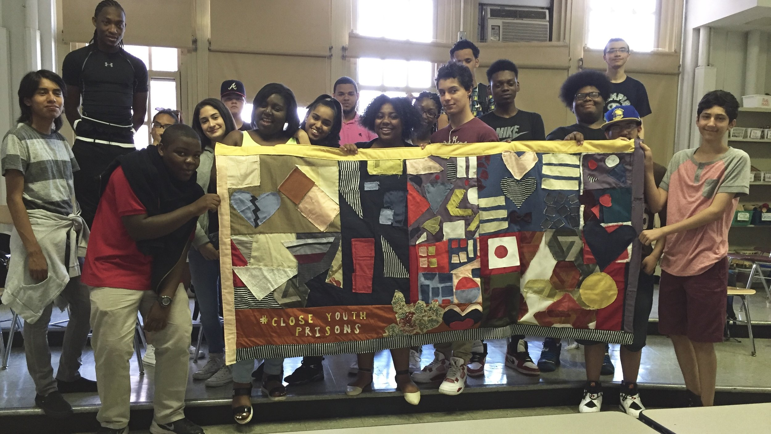Students proudly presents their quilt to advocate for the closing of youth prisons.