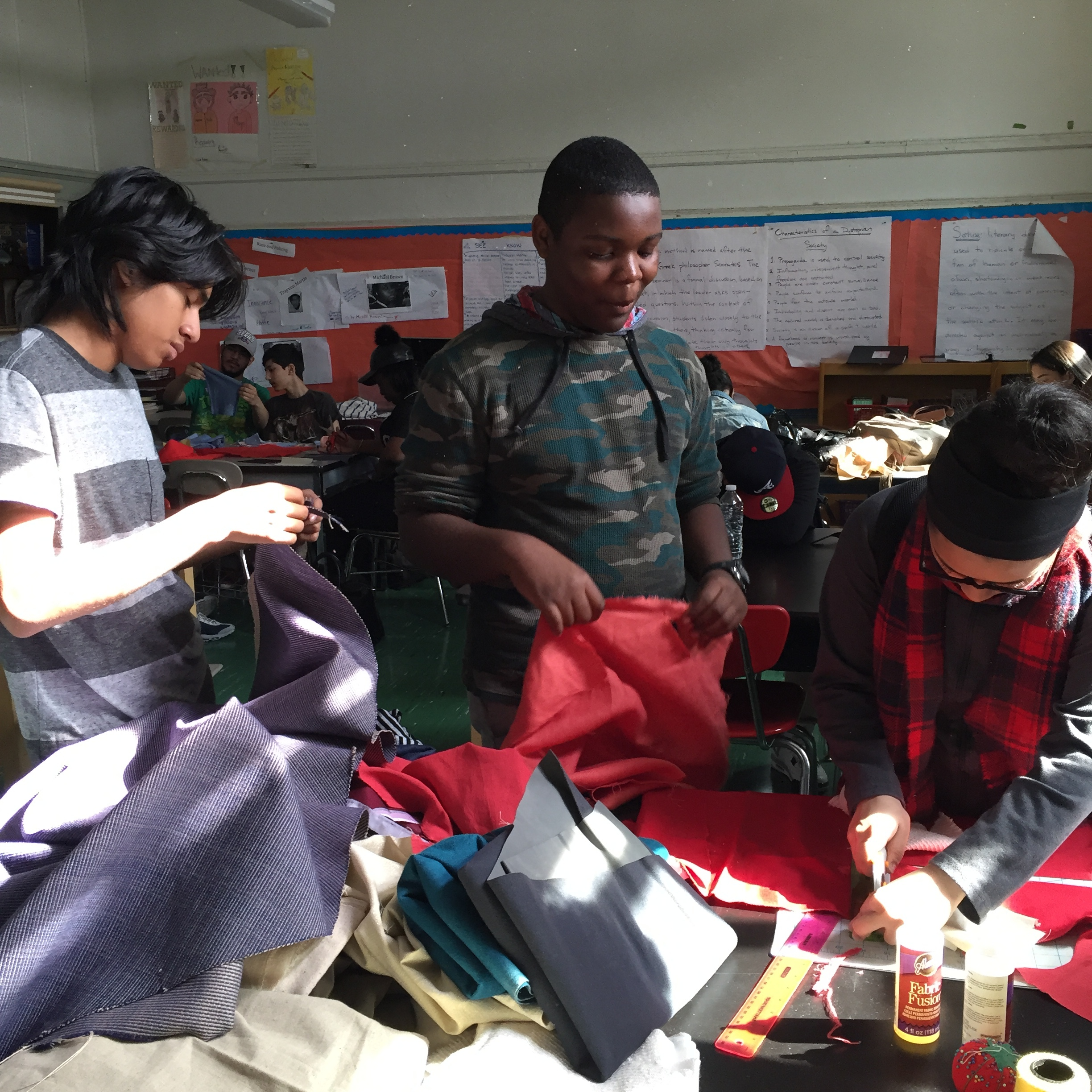 Different group of students looking for their fabric for their quilt pieces.