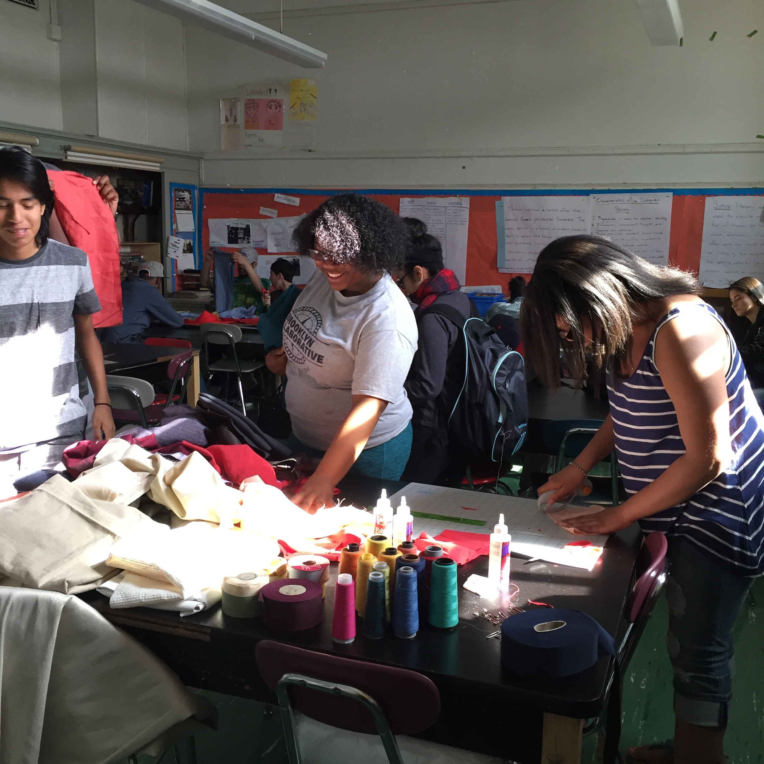 Students measuring and cutting fabric.