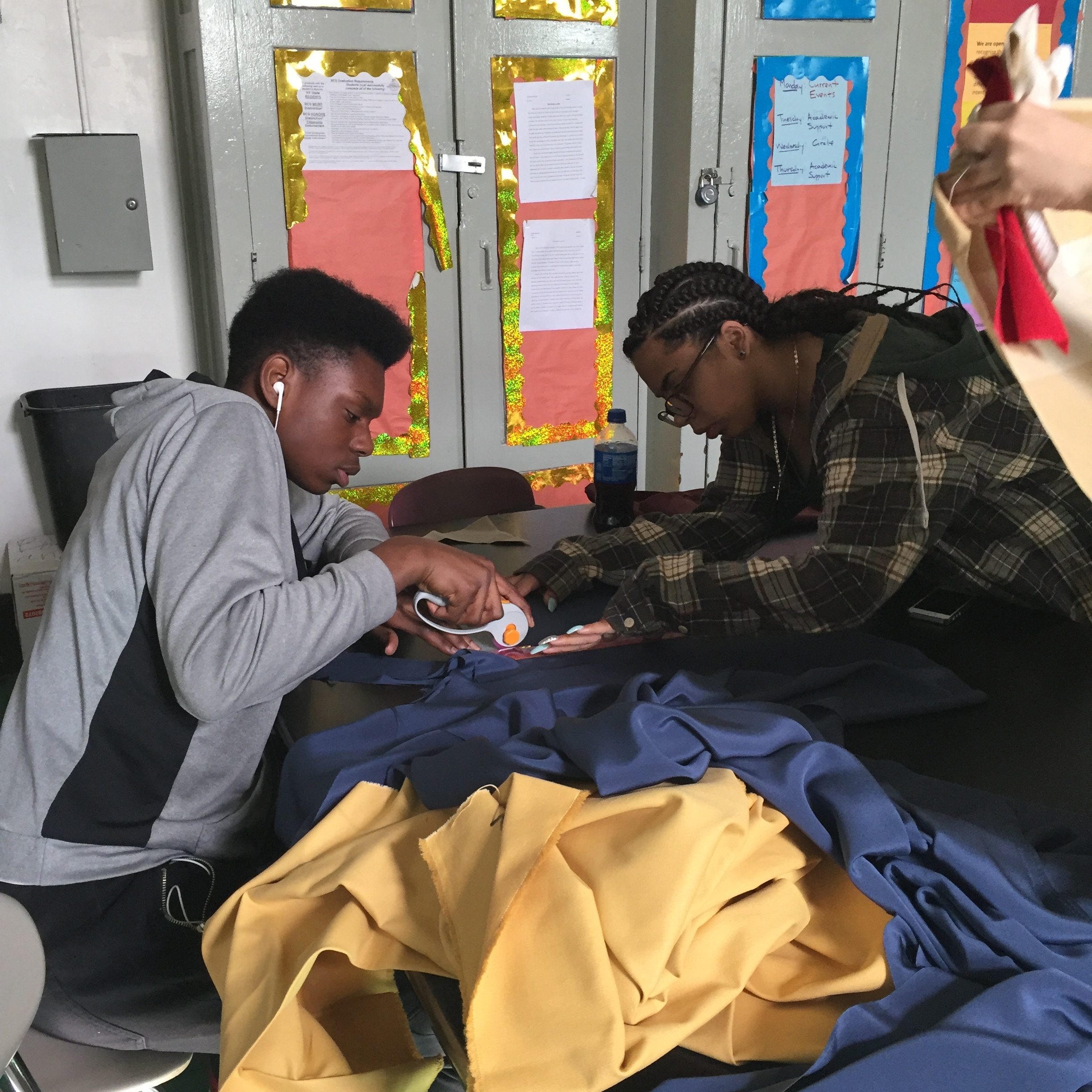 Two students helping each other cutting fabric using the rotary cutter.