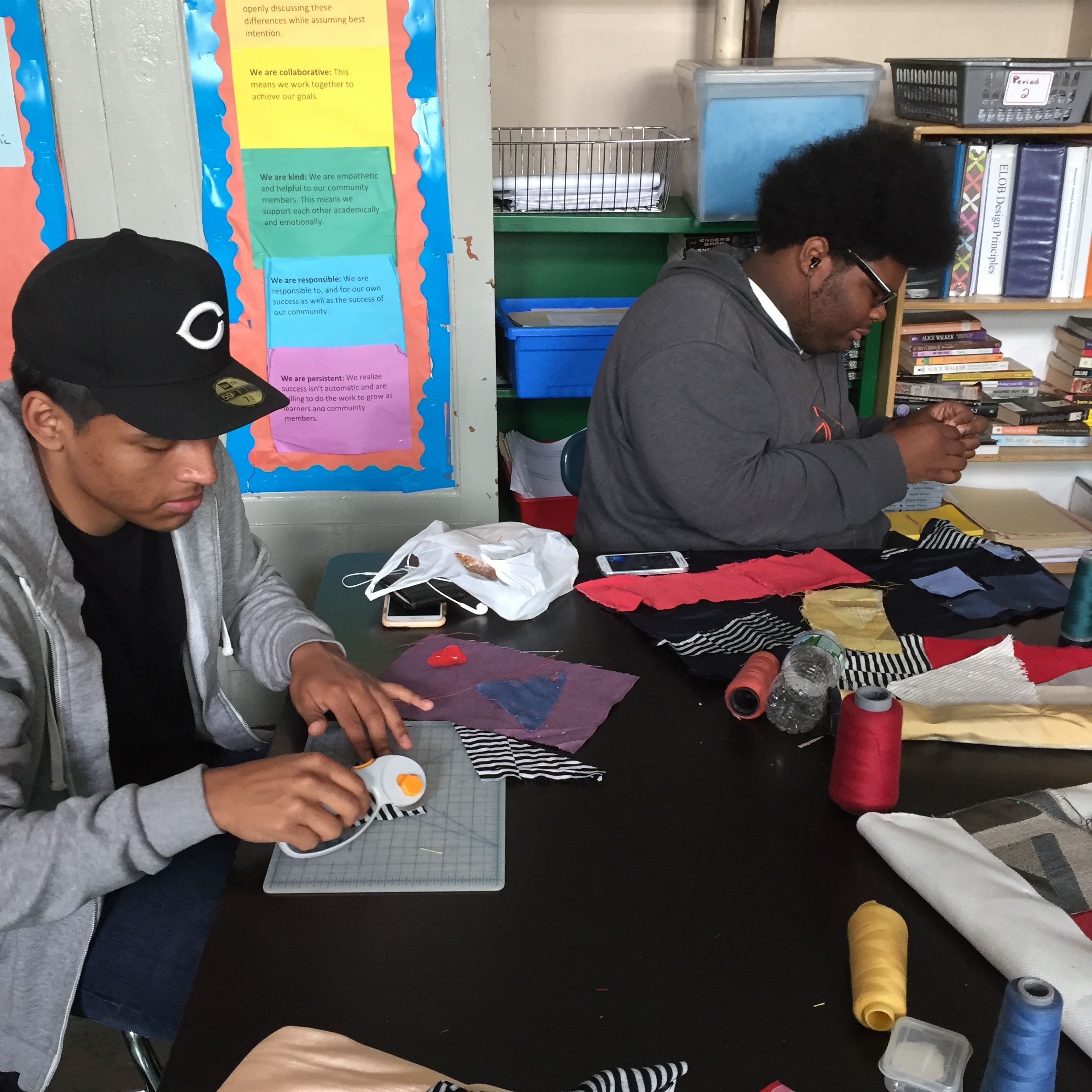 A student cutting his fabric using the rotary cutter while another student threads the needle.