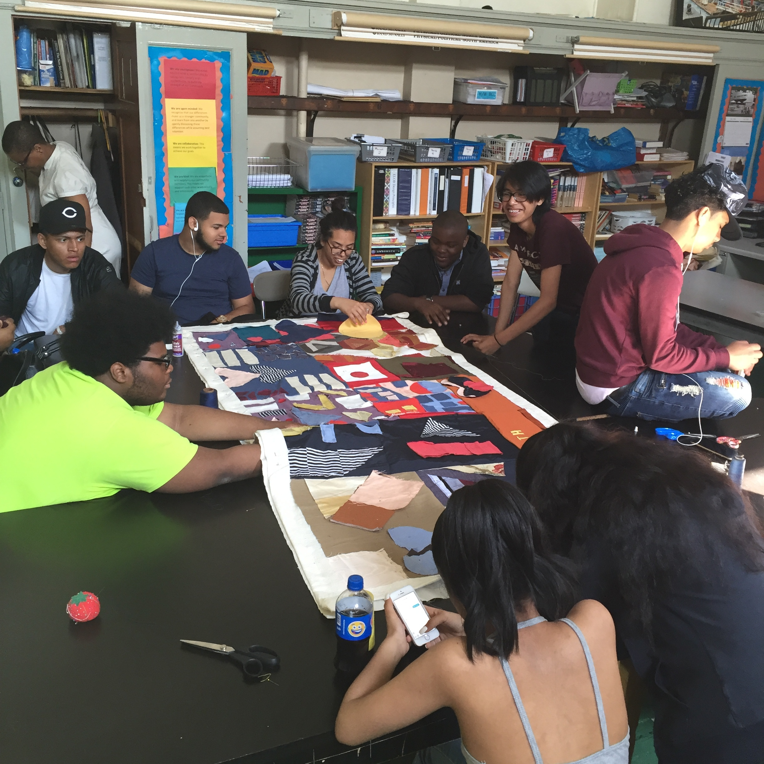 Students sit around a big table to hand sew the quilt together.